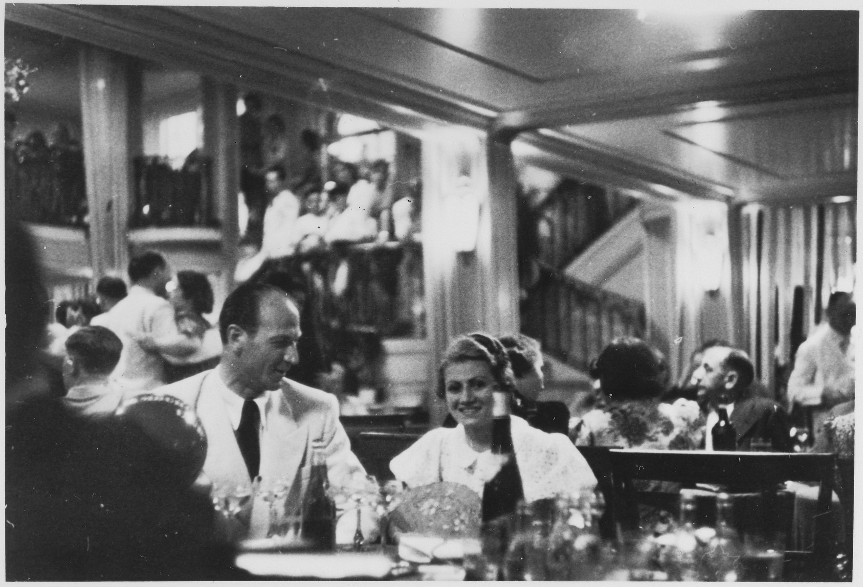 An unidentified couple enjoys a festive evening in the mirrored salon of the MS St. Louis.  Another couple dances in the background.