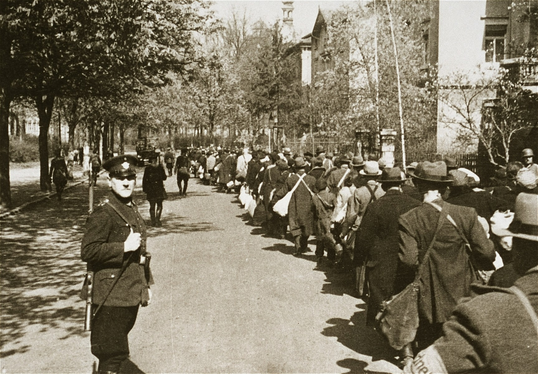 Jewish deportees, carrying a few personal belongings in bundles and suitcases, march through town along the Hindenburgstrasse from the assembly center at the Platzscher Garten to the railroad station.