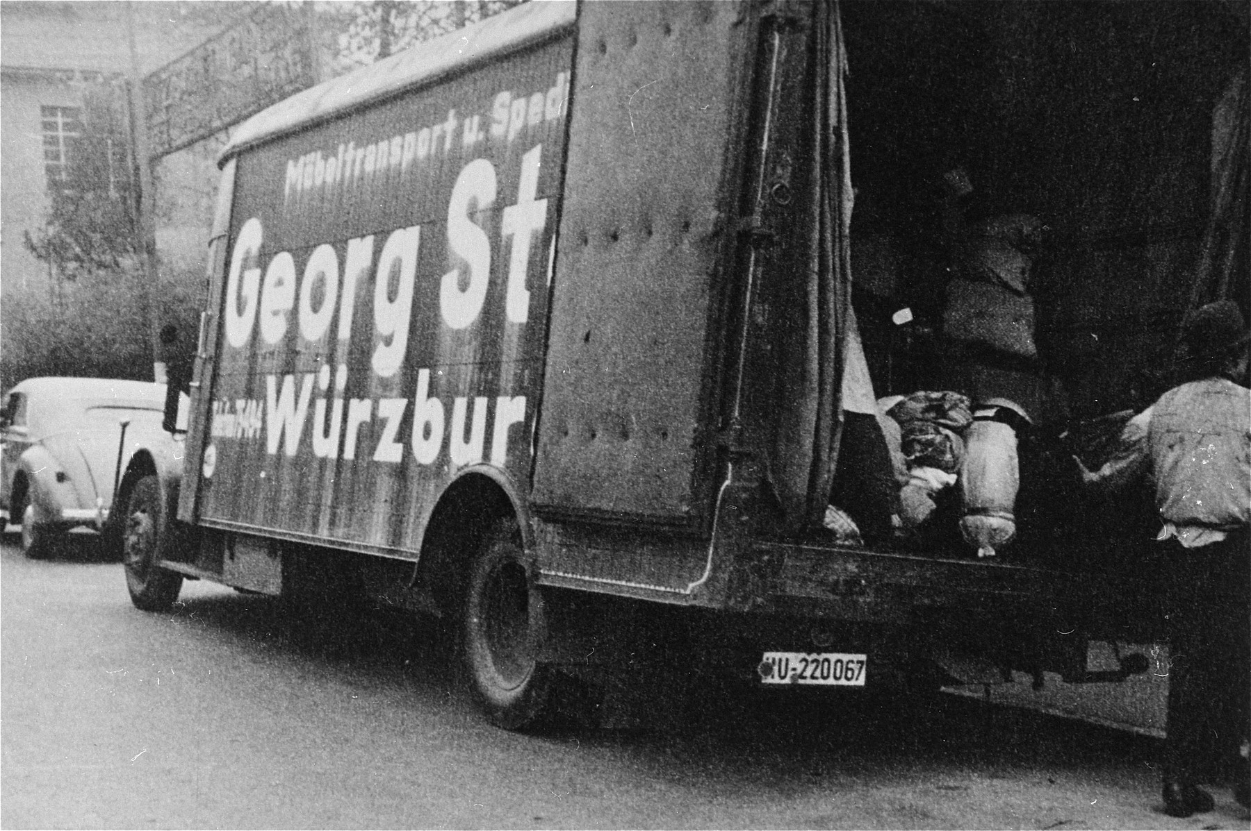 The bundles and suitcases of the Jewish deportees are loaded onto a moving van.