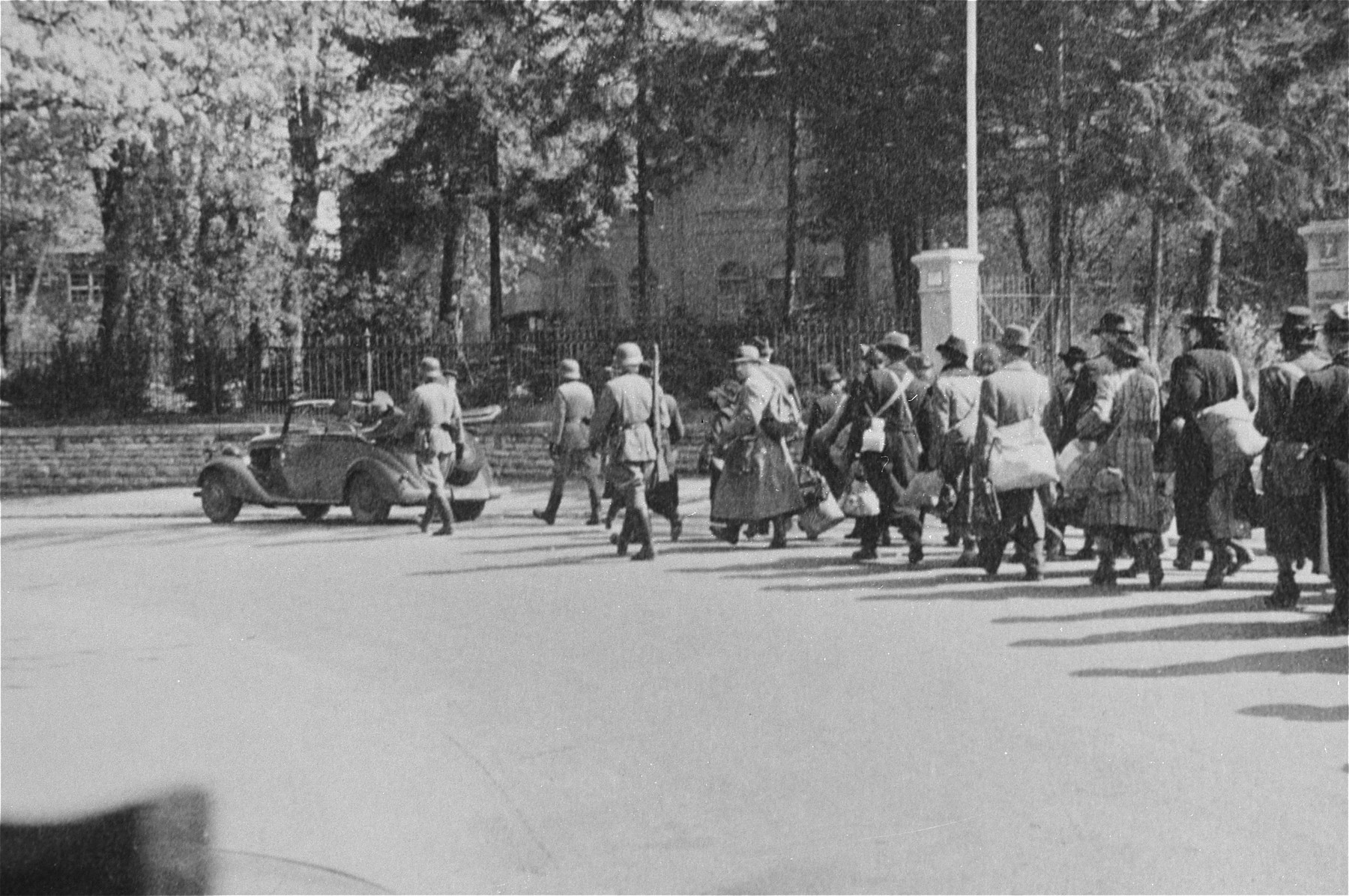 Jewish deportees, carrying bundles and suitcases, march through town toward the railroad station behind Nazi officials riding in an open car.