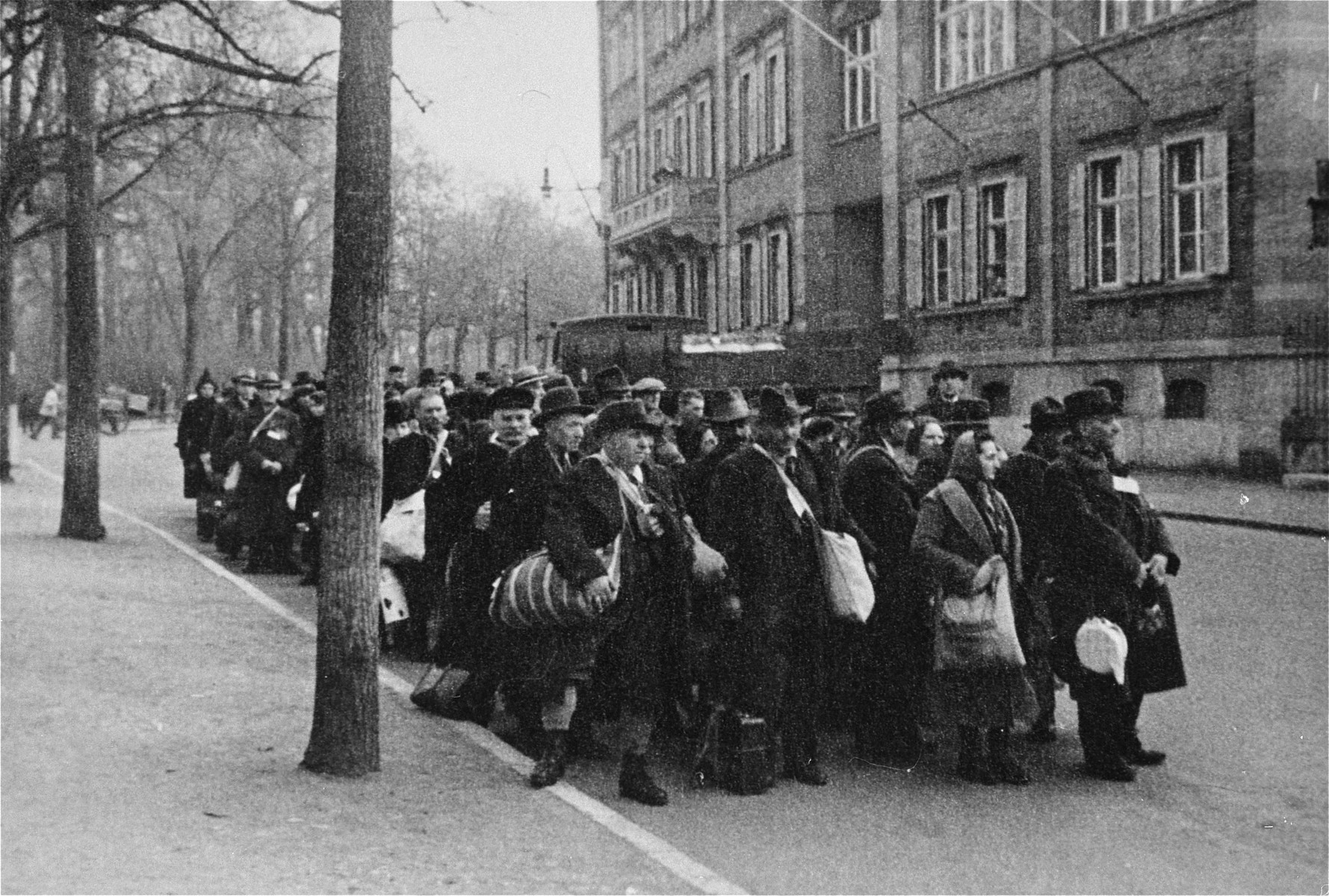 Jewish deportees, carrying a few personal belongings in bundles and suitcases, march through town from the assembly center at the Platzscher Garten to the railroad station.
