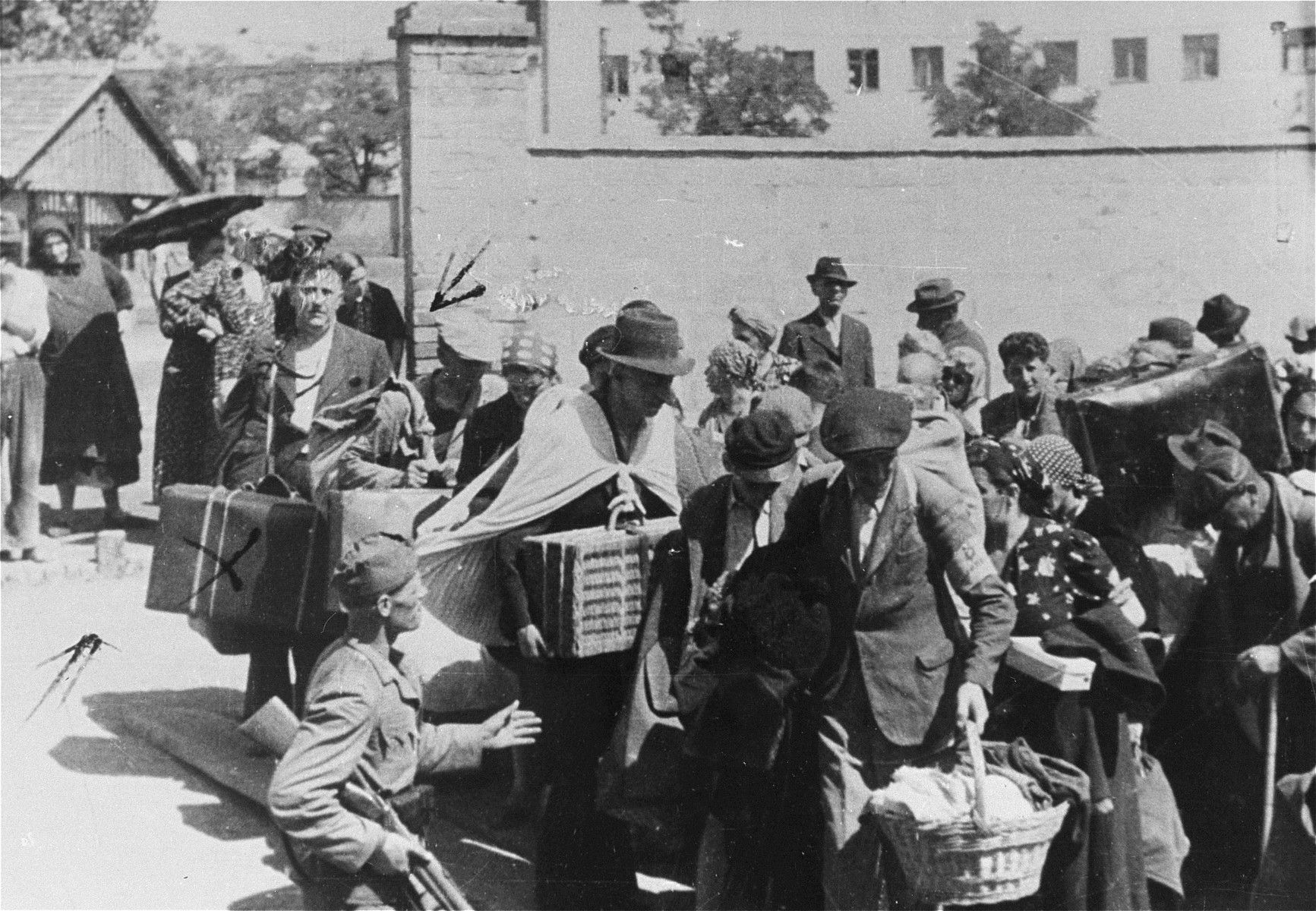 Jews carrying suitcases and baskets, are rounded-up for deportation from Zrenjanin, Serbia.