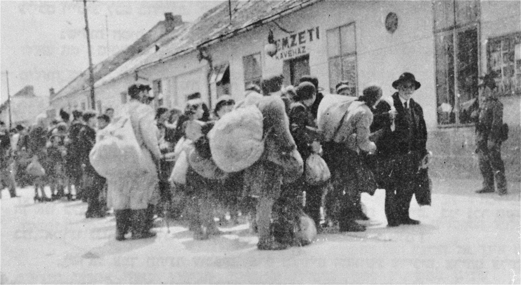 Deportation from Dunaszerdahely [Dunaska Streda].  Jews march along the Obizag Utca [Star Street] on their way to the train station.