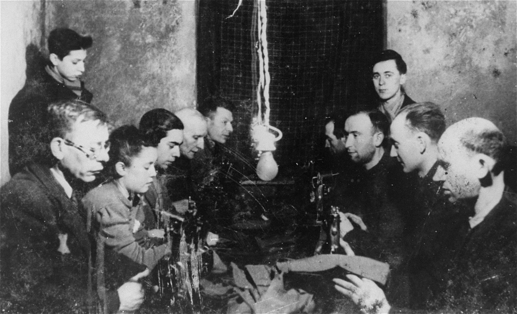 Jews sit a worktable sewing hats in a workshop in the Lodz ghetto.