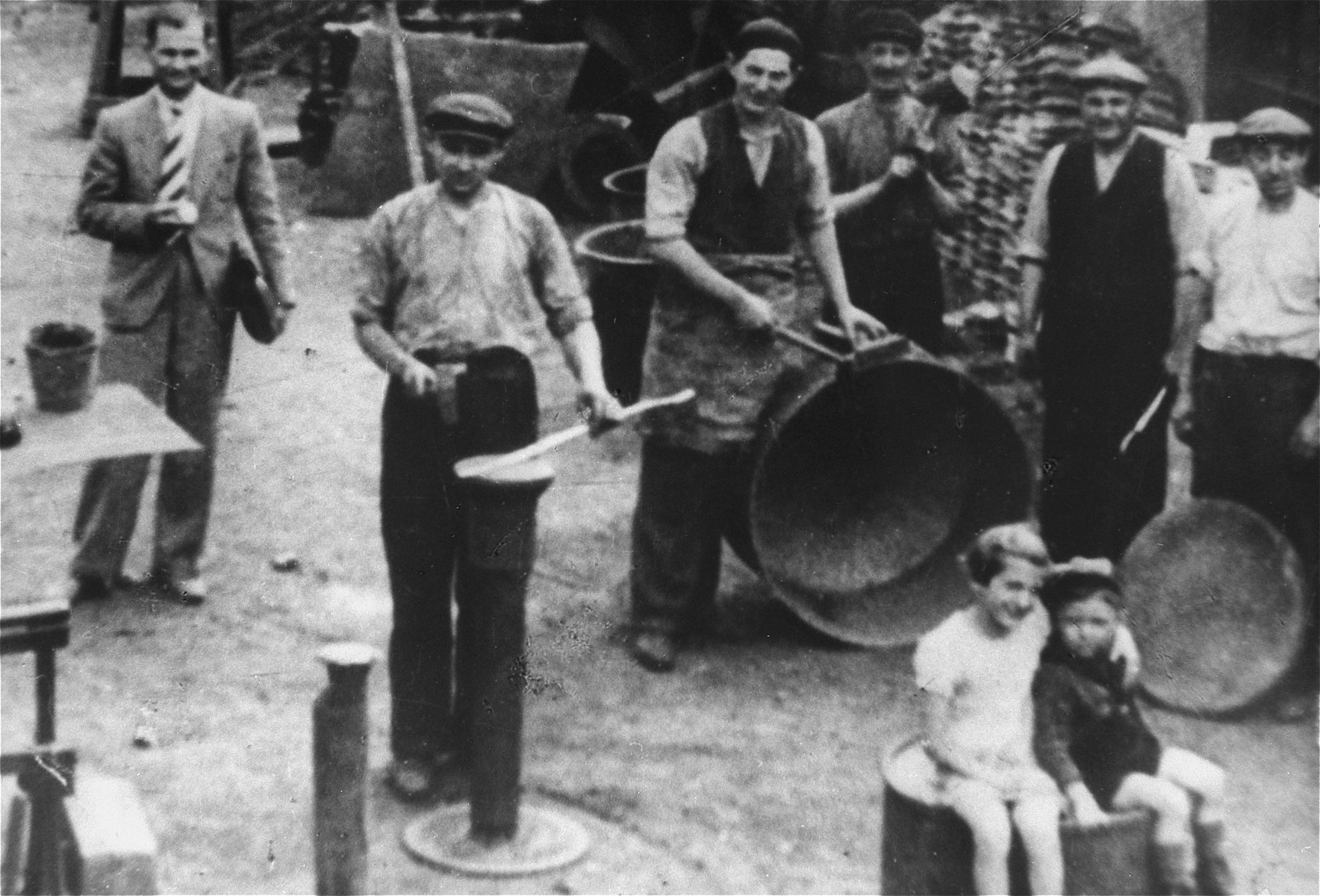 Jews stand among large pots outside a workshop in an unidentified town or ghetto.