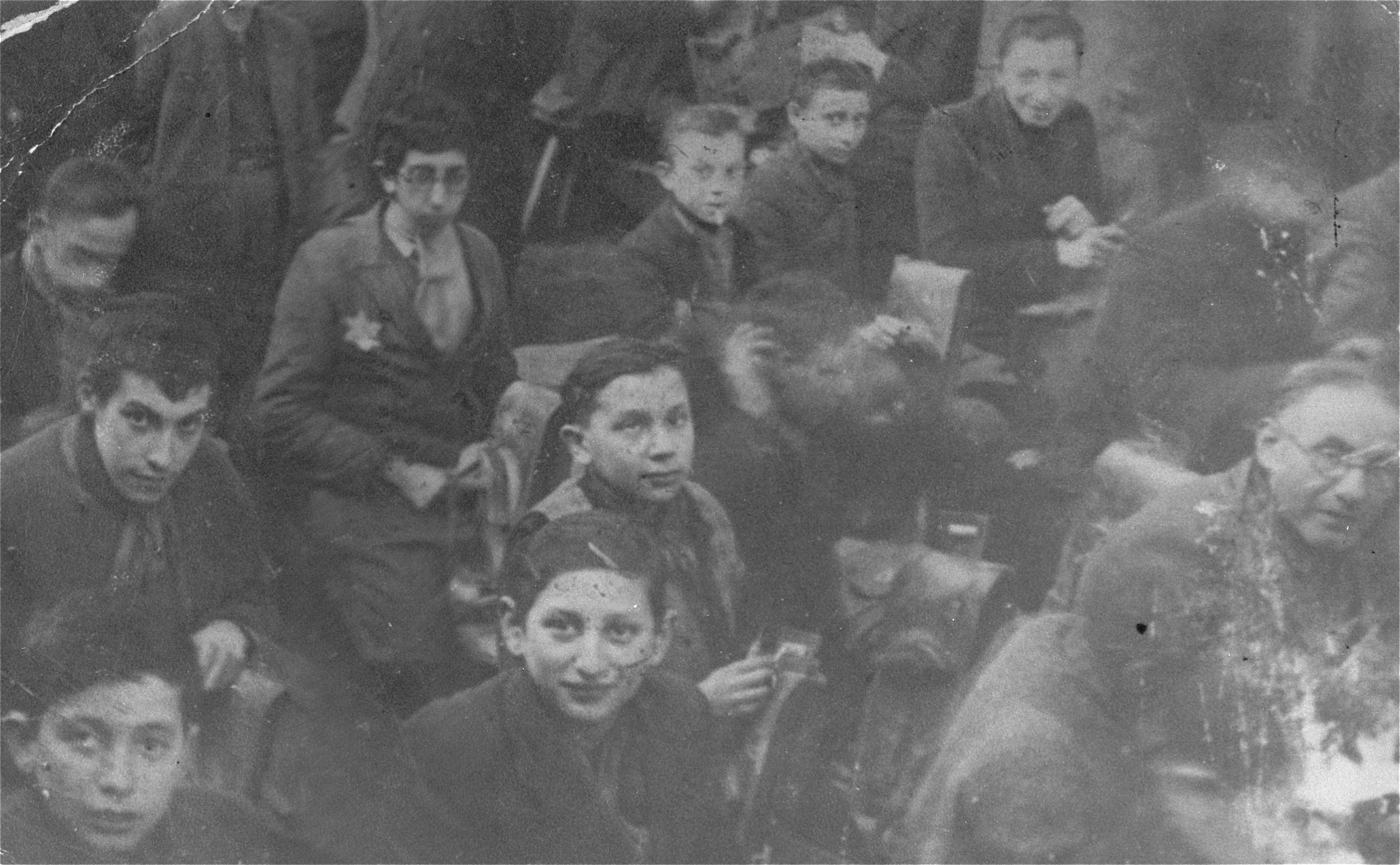 Adults and children work in a harness-making workshop in the Lodz ghetto.  Lajb Majerowicz is pictured in the upper right corner.