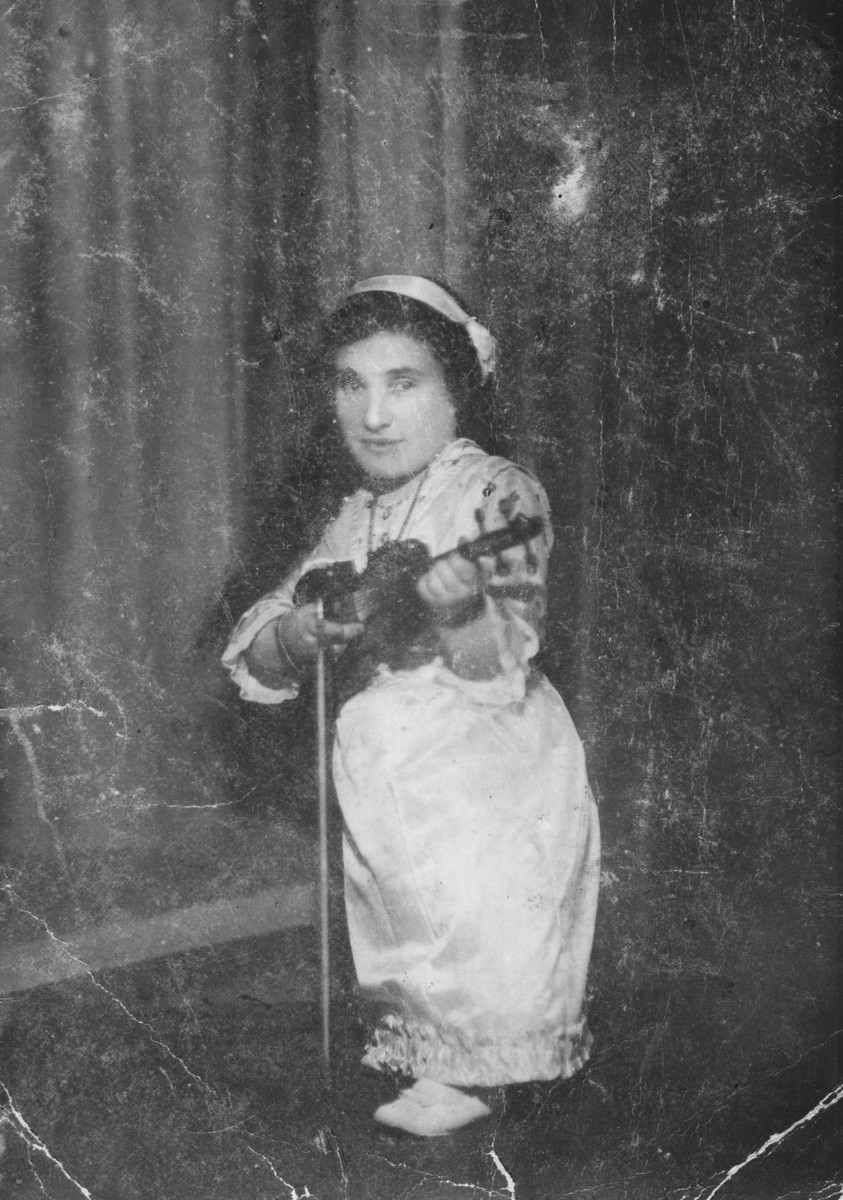 A member of a family of Jewish dwarf entertainers who survived Auschwitz, posing with her violin.
