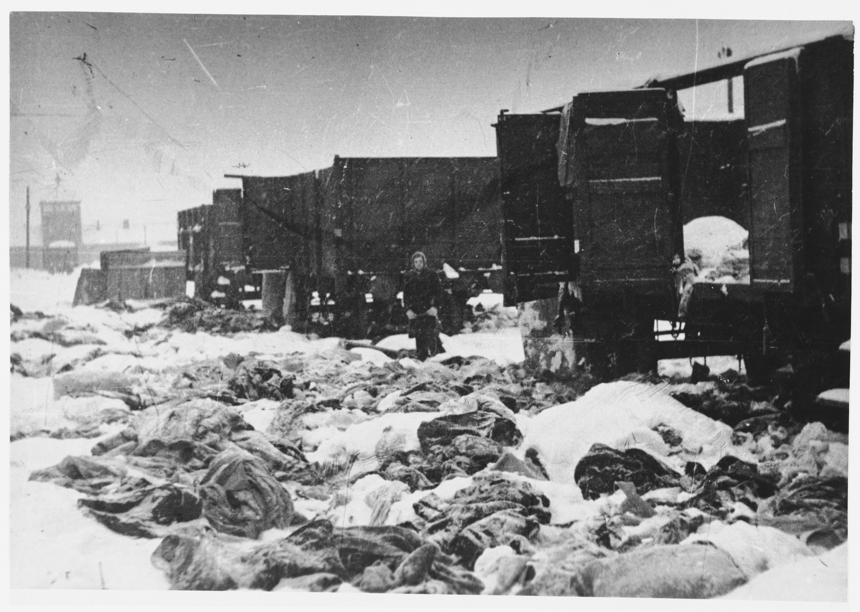 """A shipment of bedding, partially covered with snow, lies strewn next to an abandoned train in Auschwitz-Birkenau immediately after the liberation.  Original caption:  """"The shipment of bedding (taken from the prisoners) which did not leave for the Reich."""""""