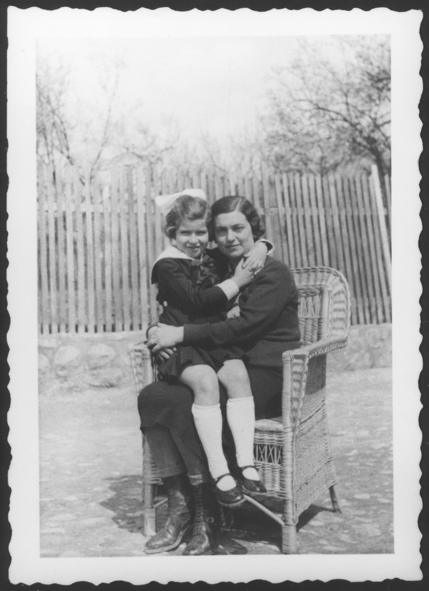 A Jewish mother and daughter pose outside their home in Moroeni, Romania, seated in a wicker chair.  Pictured are Blanka Kupfermann and her daughter Marta .