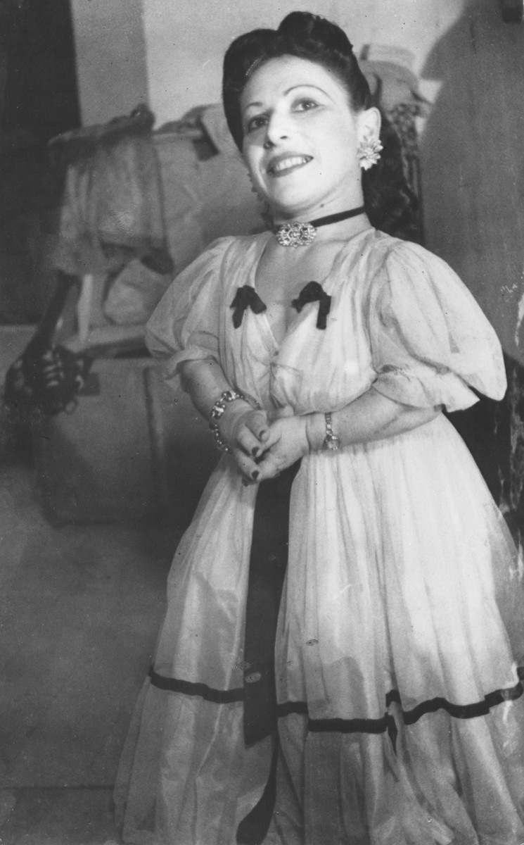 Portrait of a member of the Ovici family, a family of Jewish dwarf entertainers who survived Auschwitz, against a theatrical backdrop.  The sister pictured is Elizabeth Ovici-Moskowitz.