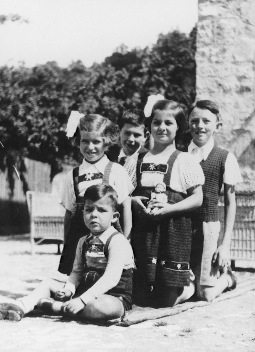 A group of children pose outside in Moroeni, Romania.  Among those pictured are  Marta (kneeling at left) and Aurel Kupfermann (far right).