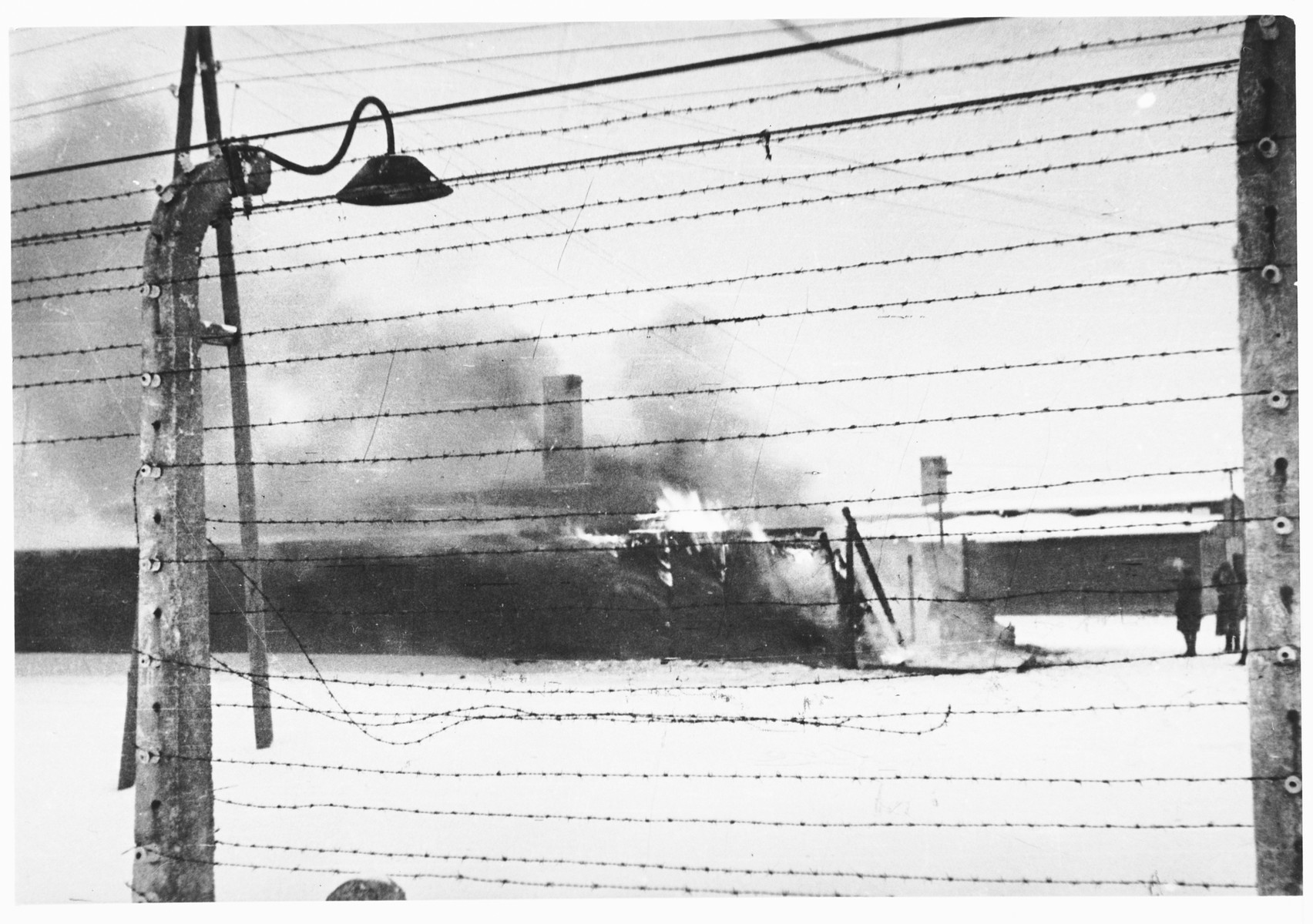 "View through the barbed wire fence of the burning Kanada barracks in Auschwitz-Birkenau immediately after the liberation.  Original caption:  ""'Kanada' burns.  Before leaving, the Germans set fire to magazines and piles of prisoner's clothing."""