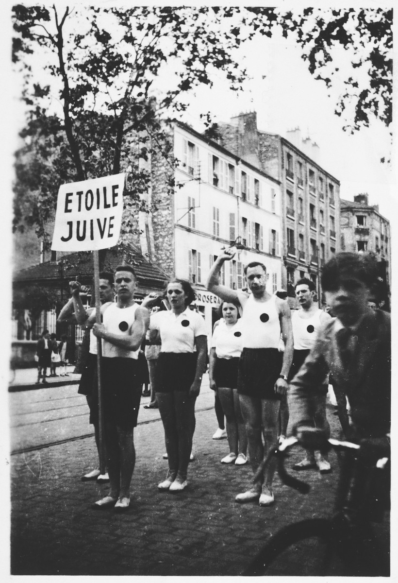Membes of the Jewish sports club, Etoile Juive, salute during a parade through Paris.