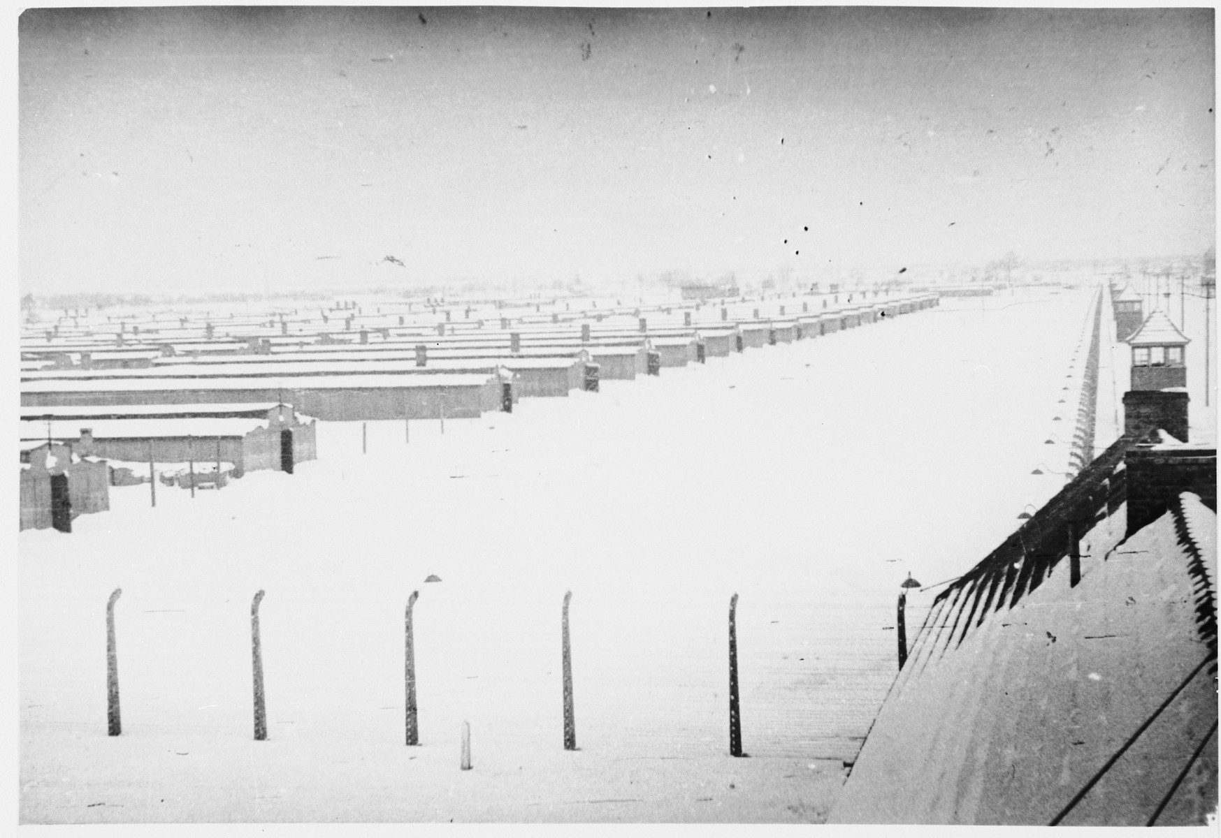"""View of Auschwitz-Birkenau under a blanket of snow immediately after the liberation.  Original caption:  """"The general view, taken from the watchtower at the main gate."""""""