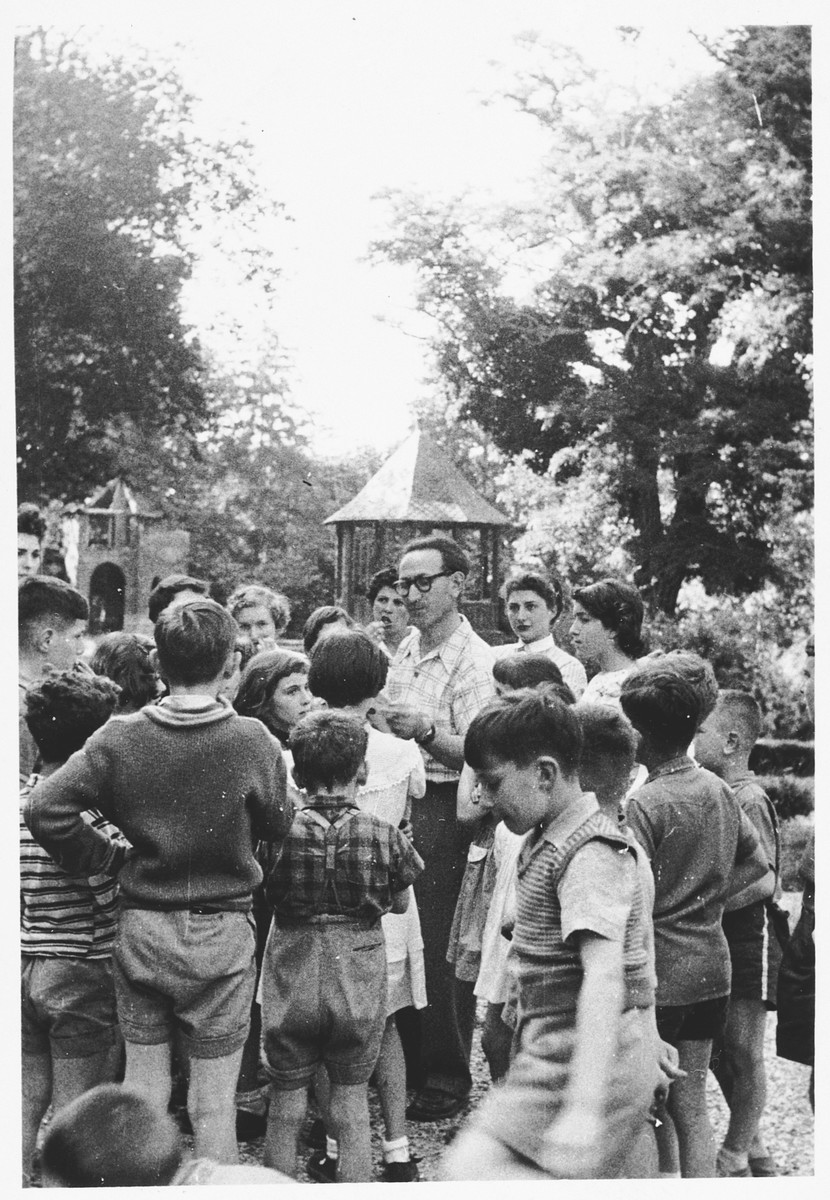 Eliezer Makovsky, director of the Nahum Aronson children's home in Les Andelys, France, talks with a group of children on the grounds of the home.