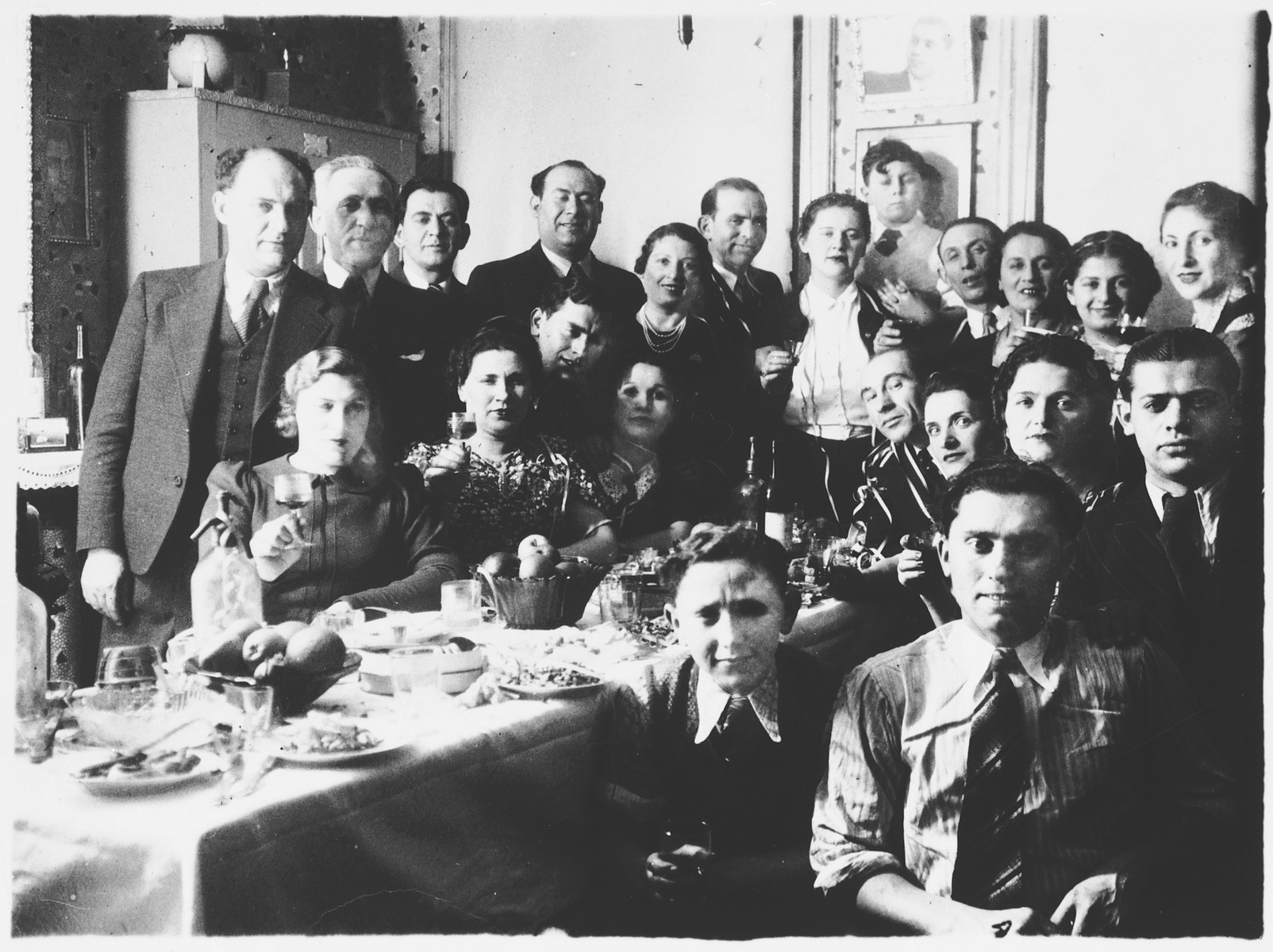 Group portrait of family and friends who have gathered to celebrate the Aufruf (pre-wedding ceremony) of Leah Mendelowicz and Alex Ciechanow.  Among those pictured are Alex Ciechanow (at the bottom right), Leah Mendelowicz (second row from the front, third from the right), and Fani Mendelowicz (second row from the front, second from the right).