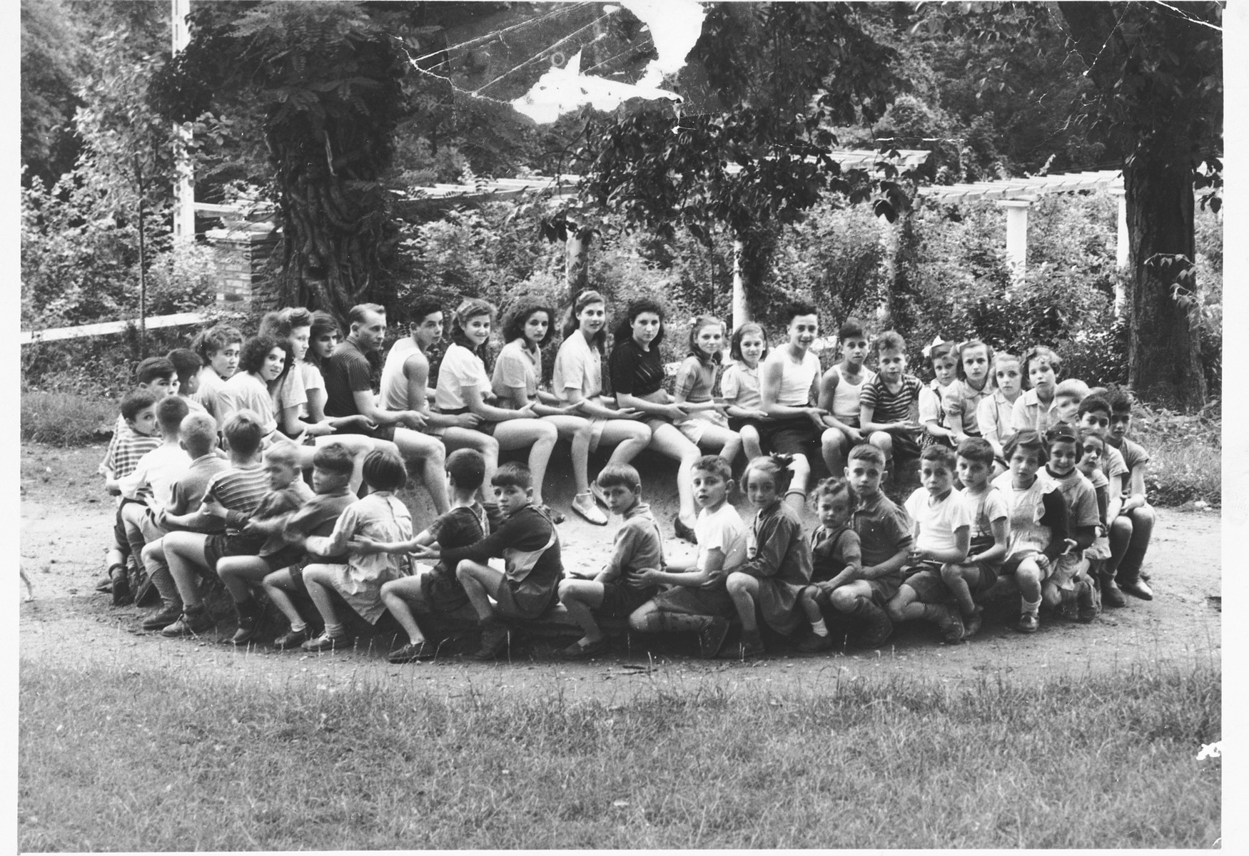 Staff and children pose in a large circle on the grounds of the Nahum Aronson children's home in Les Andelys, France.