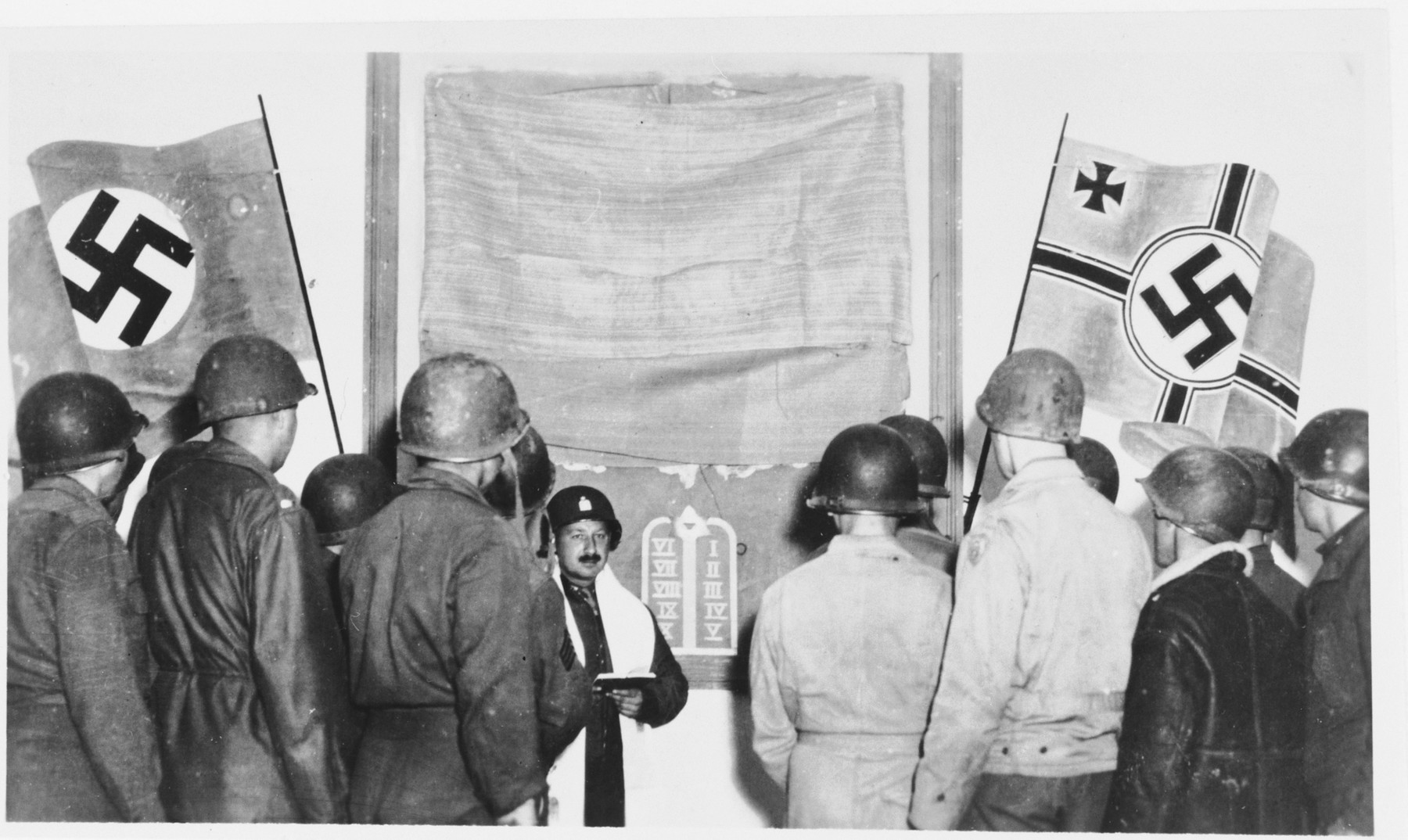 Jewish soldiers in the U.S. army hold religious services in a room decorated with Nazi flags.