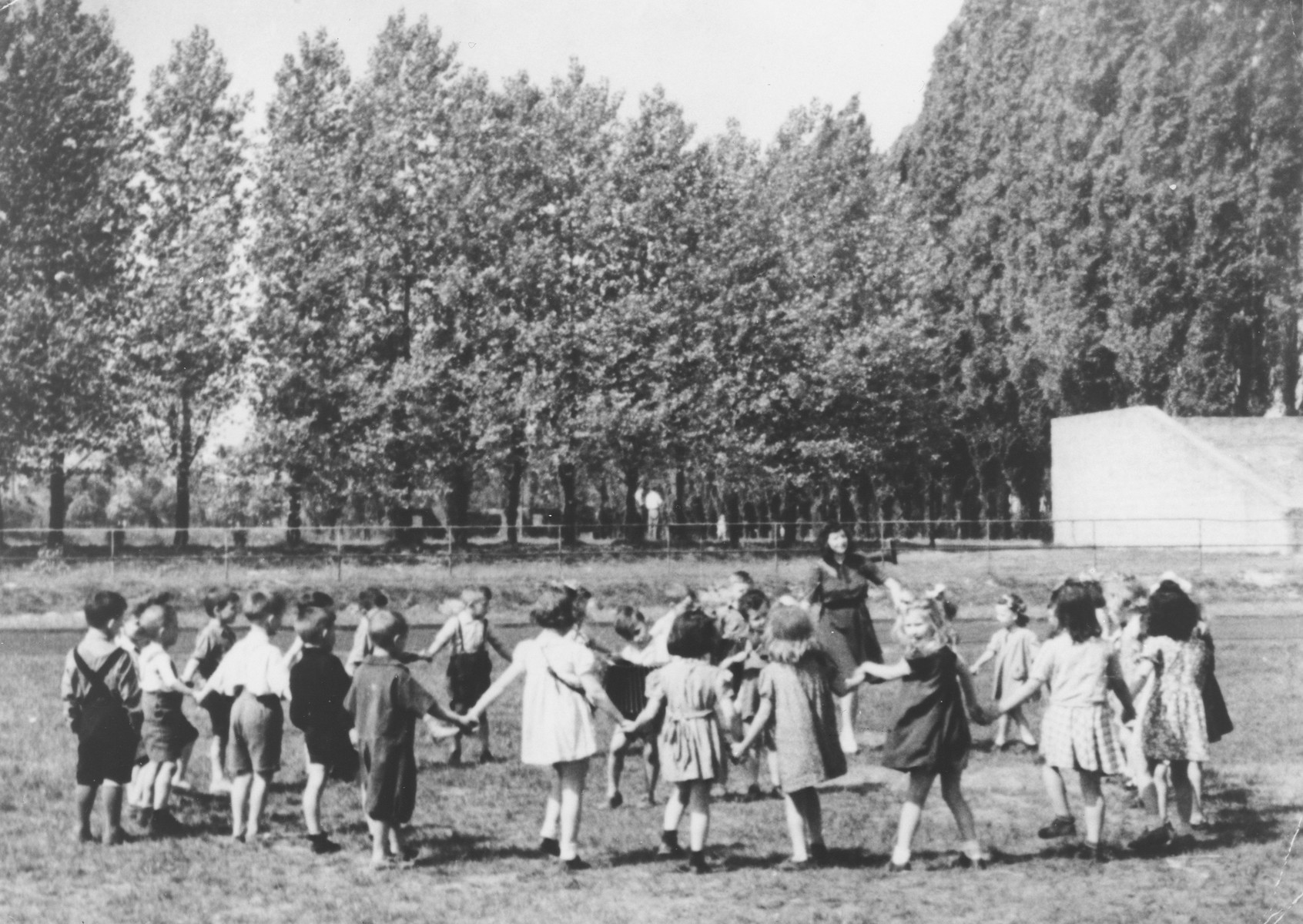 Preschoolers in the Mariendorf displaced persons camp dance in a circle.  Those pictured include Maya Rosenfeld (later Freed Brown).