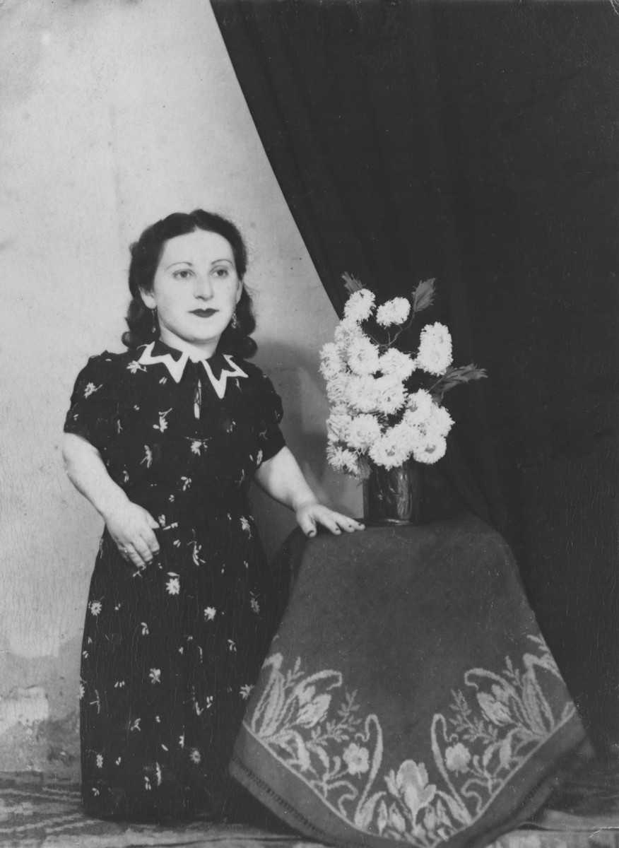 Portrait of a member of the Ovici family, a family of Jewish dwarf entertainers known as the Lilliput Troupe, who survived Auschwitz, next to a vase of flowers.  Pictured is Elizabeth Ovici-Moskowitz.