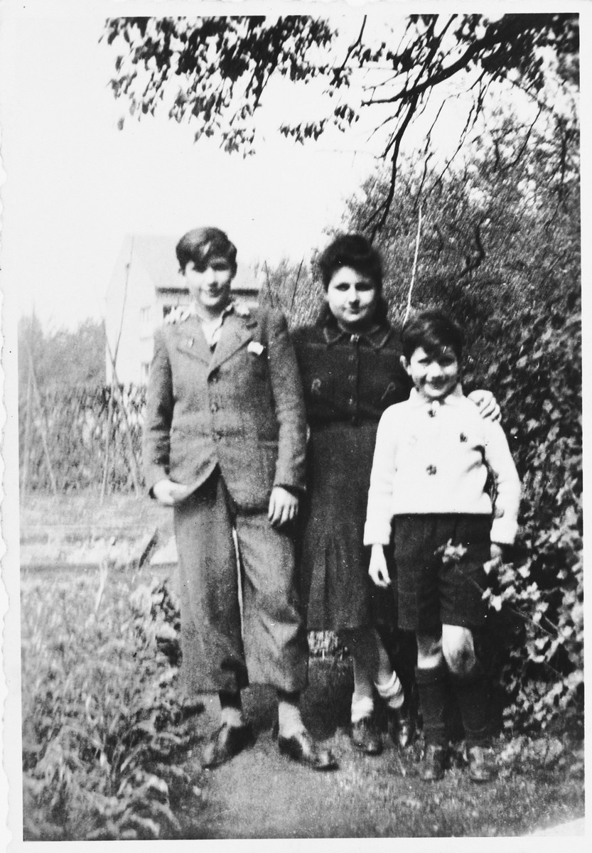 The three older Rotenberg siblings pose in a garden while in hiding in Beligium.  Pictured are Wolfgang, Regina, and Siegmund.