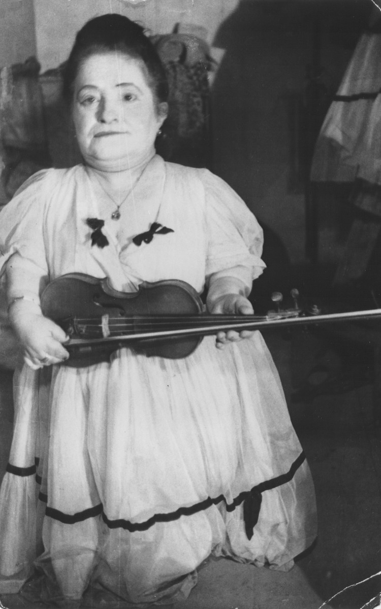 Portrait of Rozika Ovici, a member of a family of Jewish dwarf entertainers who survived Auschwitz, holding her violin.