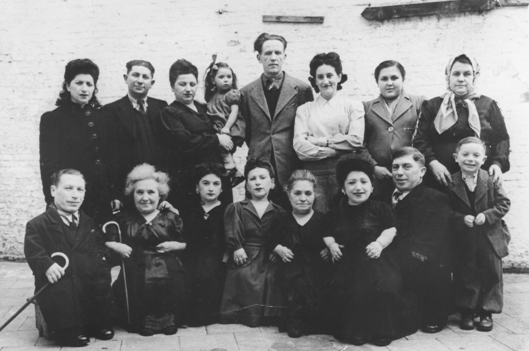 Group portrait of the Ovici family, a family of Jewish dwarf entertainers who survived Auschwitz.  Seated from left to right are Micki, Francesca, Perla, Elizabeth, Rozika, Frieda, Avram and Shimshon.  Standing are Sarah, Azriel, his wife Leah holding their daughter Batia, Moshe Moskowitz (who is Elizabeth's husband), an unknown woman, Avram's daughter Batia and her mother Dora.