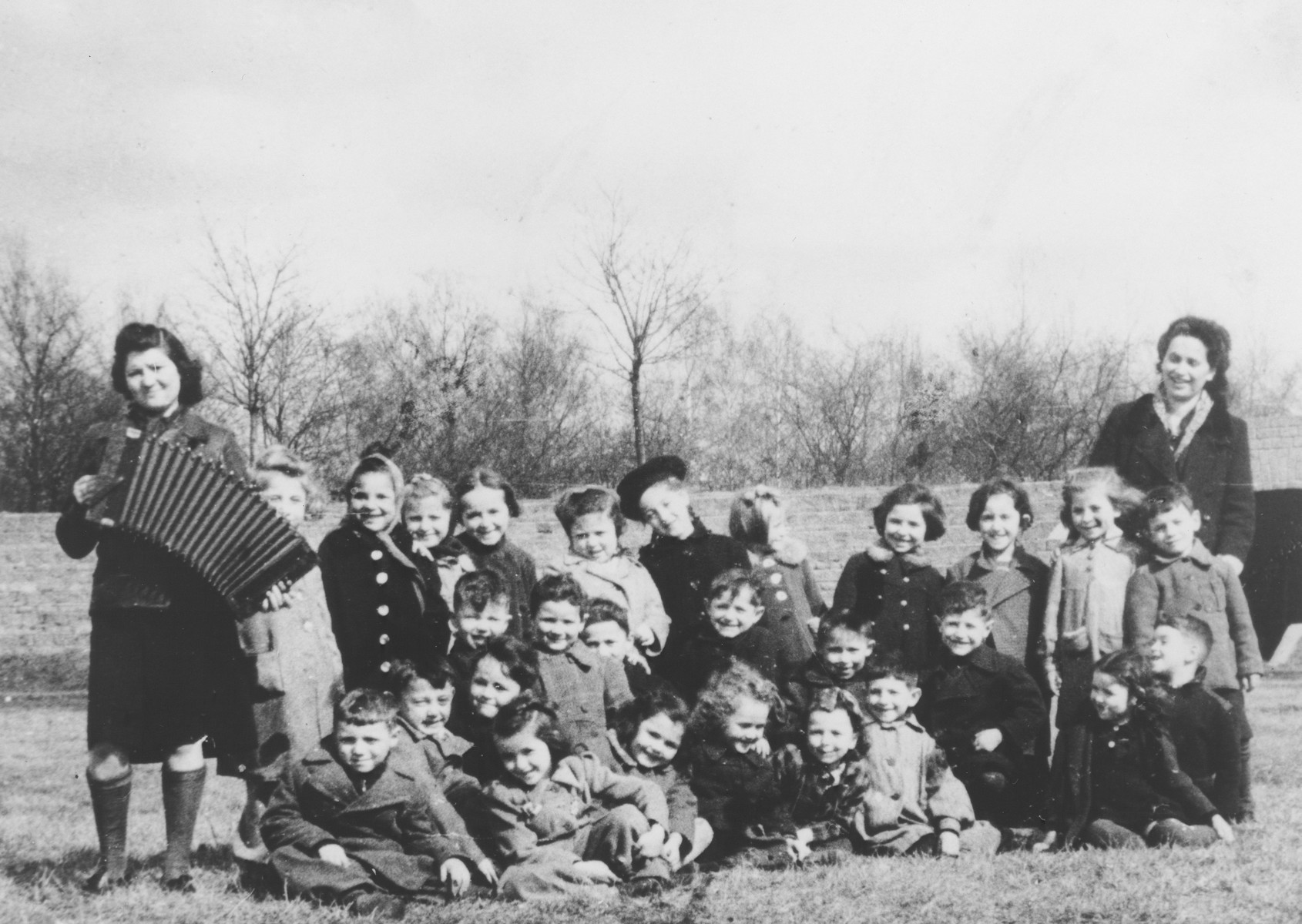 Preschoolers in the Mariendorf displaced persons camp enjoy the music of an accordian.  Those pictured include Maya Rosenfeld (later Freed Brown).