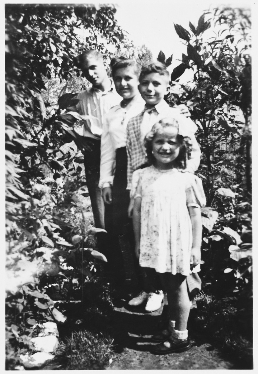 The four Rotenberg siblings pose in a garden while in hiding in Beligium.  From back to front are Wolfgang, Regina, Siegmund and Sonja.