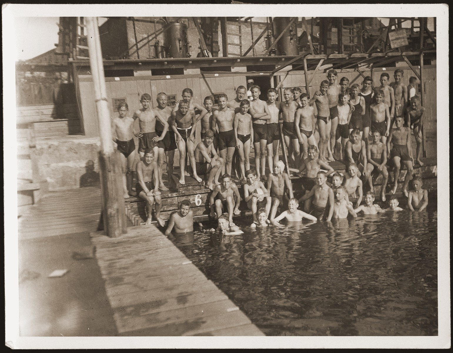 Group portrait of the swim team of the Schiller Real Gymnasium in Stettin.  Walter Jacobsberg is pictured on the far left in the pool.