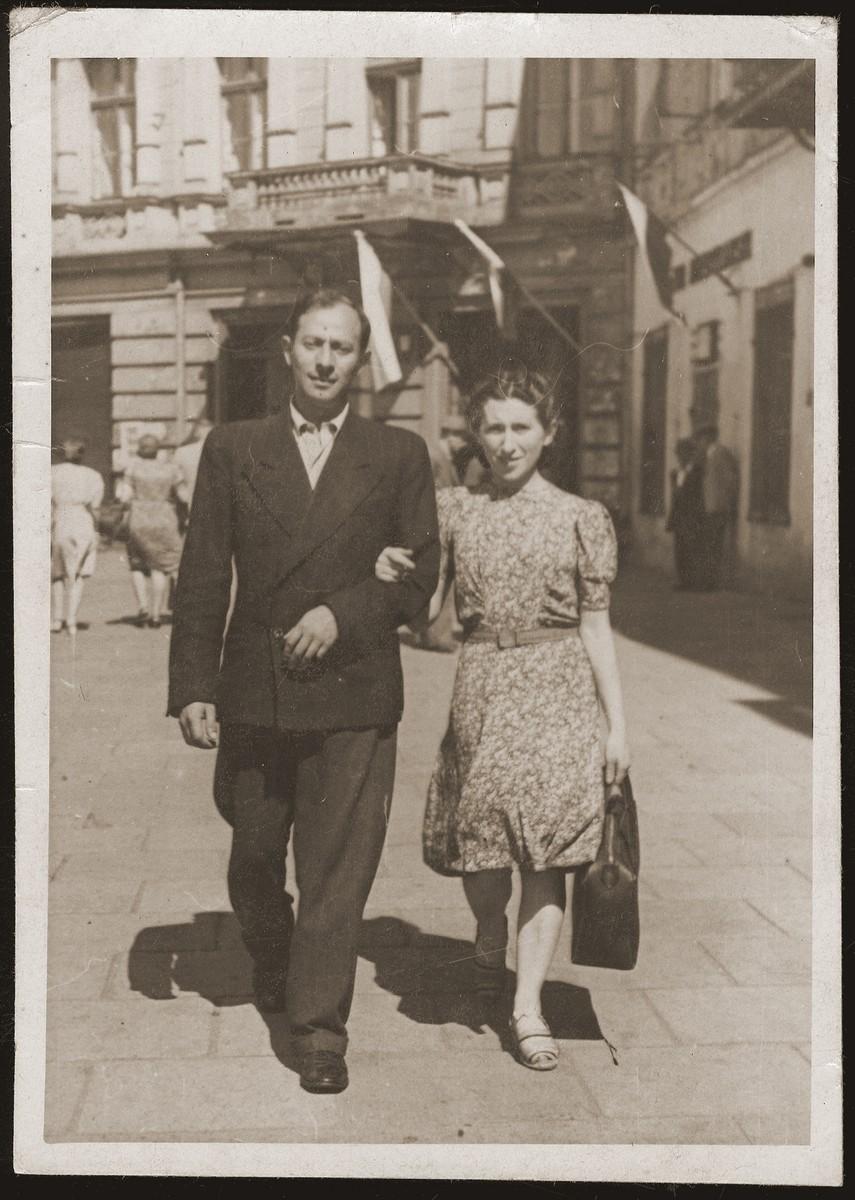 Mania Gryniewicz walks in the street with her husband, Gutman.