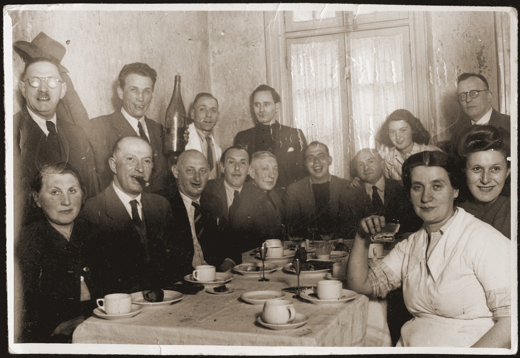 Jewish refugees at a birthday party in Shanghai.    Albert Jakobsberg and Herbert Feibel are pictured seated fifth and sixth from the left respectively. The woman sitting in the front left side, wearing white, is Adele Lowenthal, Hanne Lowenthal's sister.
