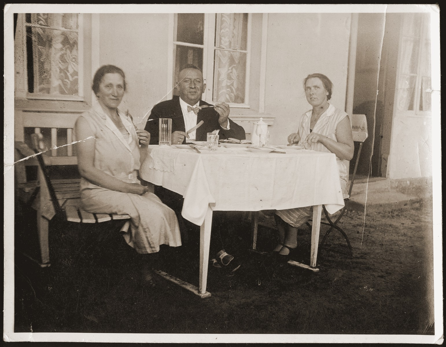 Siegfried and Betti Jacobsberg eat a meal in their garden with their German maid, Minna.