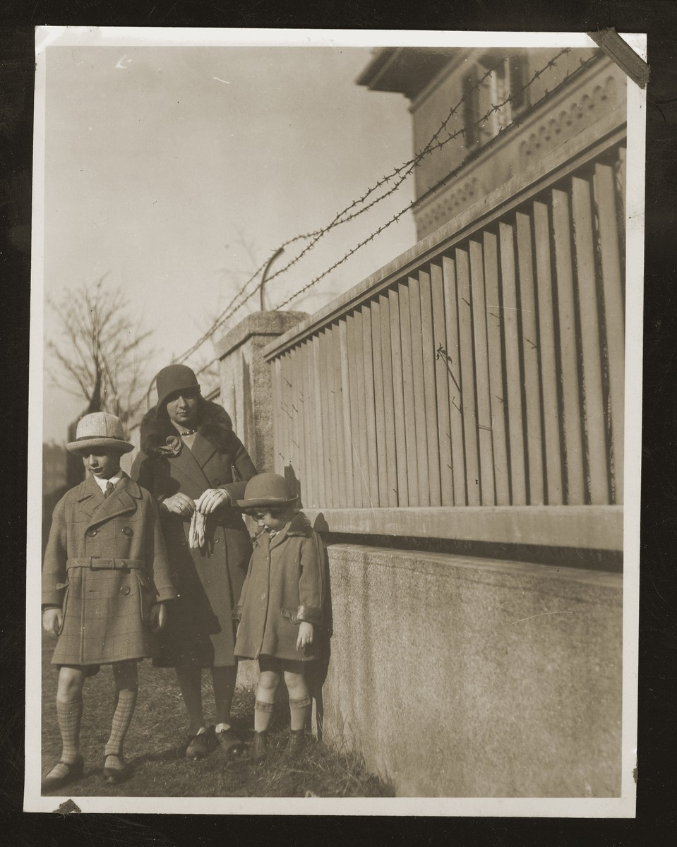 Mathilde Siegel poses by a fence with her two children Hans Peter and Maria Beate.