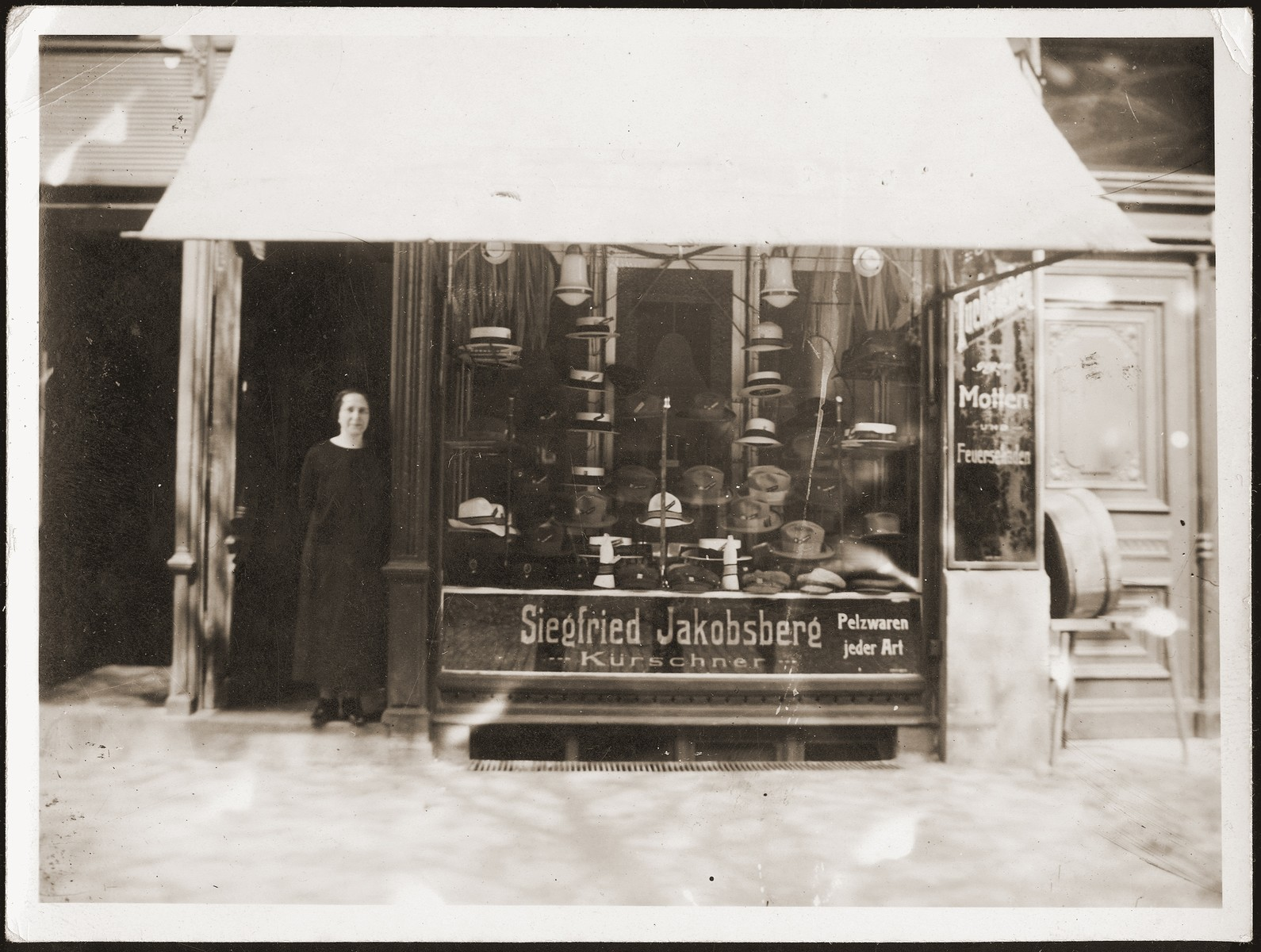 Betti Jacobsberg stands in the doorway of their fur store in Stettin.