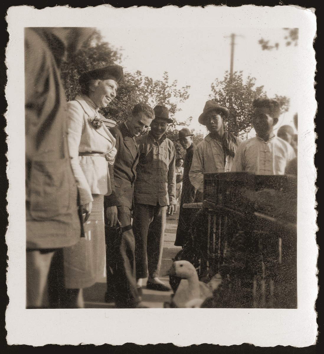 German Jewish refugees observe a Chinese wedding procession (featuring ducks) in Shanghai.  Pictured standing third and second from the left, respectively, are Walter Jacobsberg and an acquaintance, Mrs. Ehrlich.