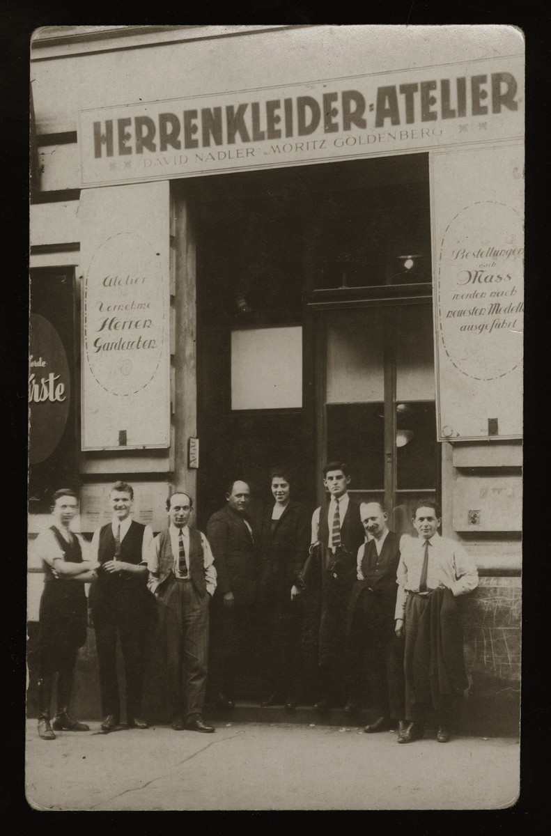Moritz Wacs (center) and his employees pose in front of his clothing and tailor shop in Vienna.