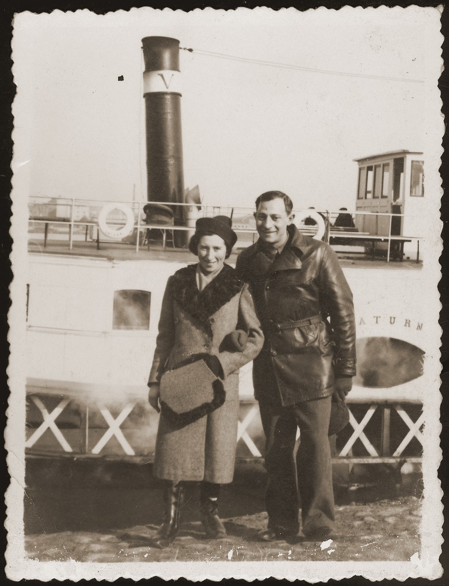 Mania and Gutman Grinewize pose in front of a boat on the Vistula river, during their visit to Warsaw.