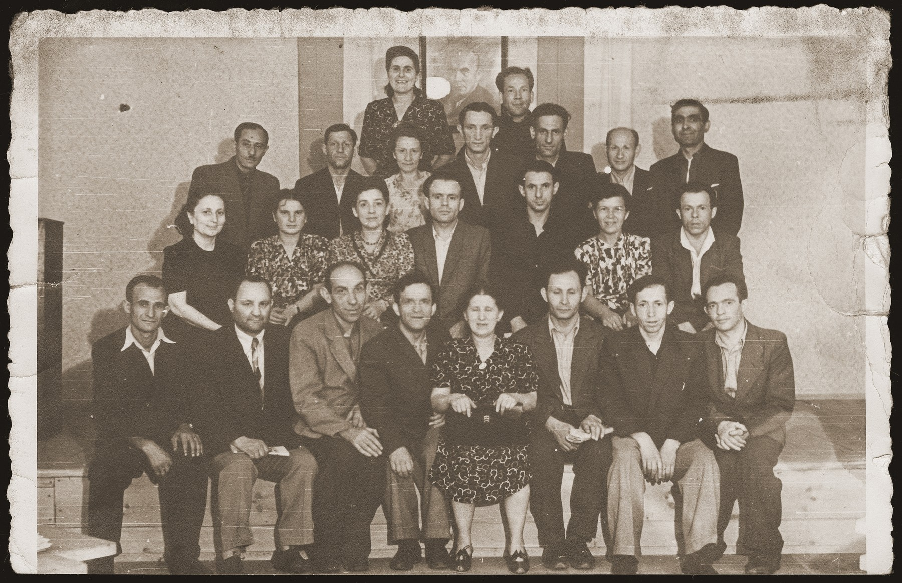 "Group portrait of Polish Jews, on a retreat in Srodborow, near Warsaw.    The portrait on the wall, behind the group is of Boleslaw Bierut, president of Poland.  Standing in the second row, first from left is Mrs. Kiwajko, wife of the editor of ""Folks Sztyme"", a Jewish daily newspaper in Yiddish."