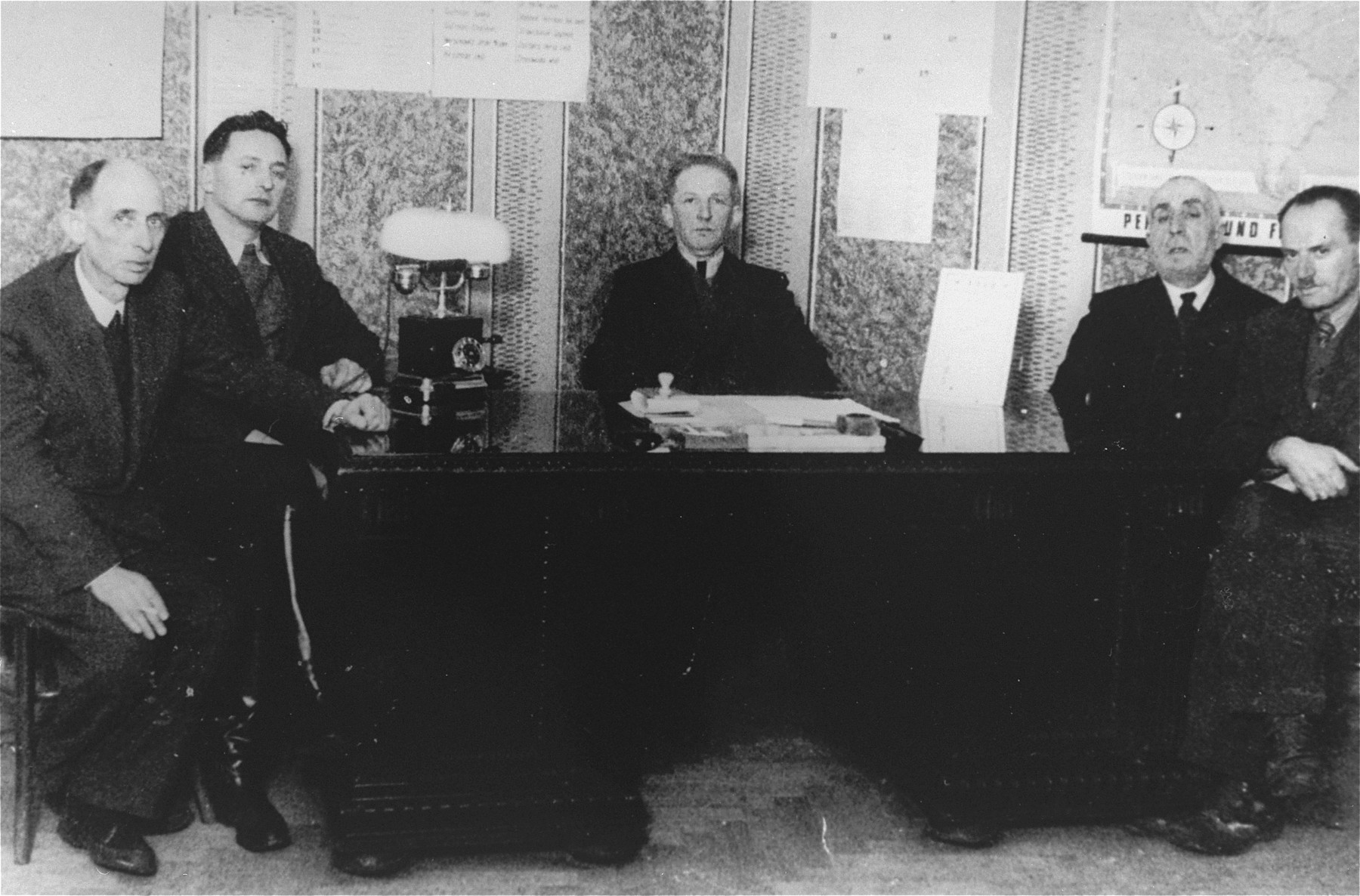 Members of the ghetto administration pose around a desk in the office of the Judenrat in the Kielce ghetto.  This photo was one the images included in an official album prepared by the Judenrat of the Kielce ghetto in 1942.