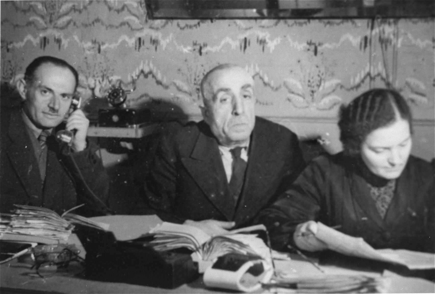 Three members of the ghetto administration sit at a table in the office of the Judenrat in the Kielce ghetto.  This photo was one the images included in an official album prepared by the Judenrat of the Kielce ghetto in 1942.