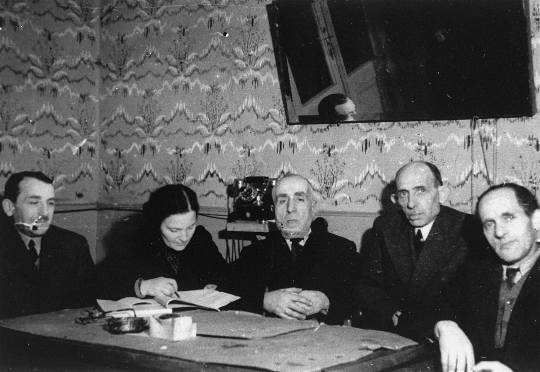 Members of the ghetto administration sit around a table in the office of the Judenrat in the Kielce ghetto.  This photo was one the images included in an official album prepared by the Judenrat of the Kielce ghetto in 1942.