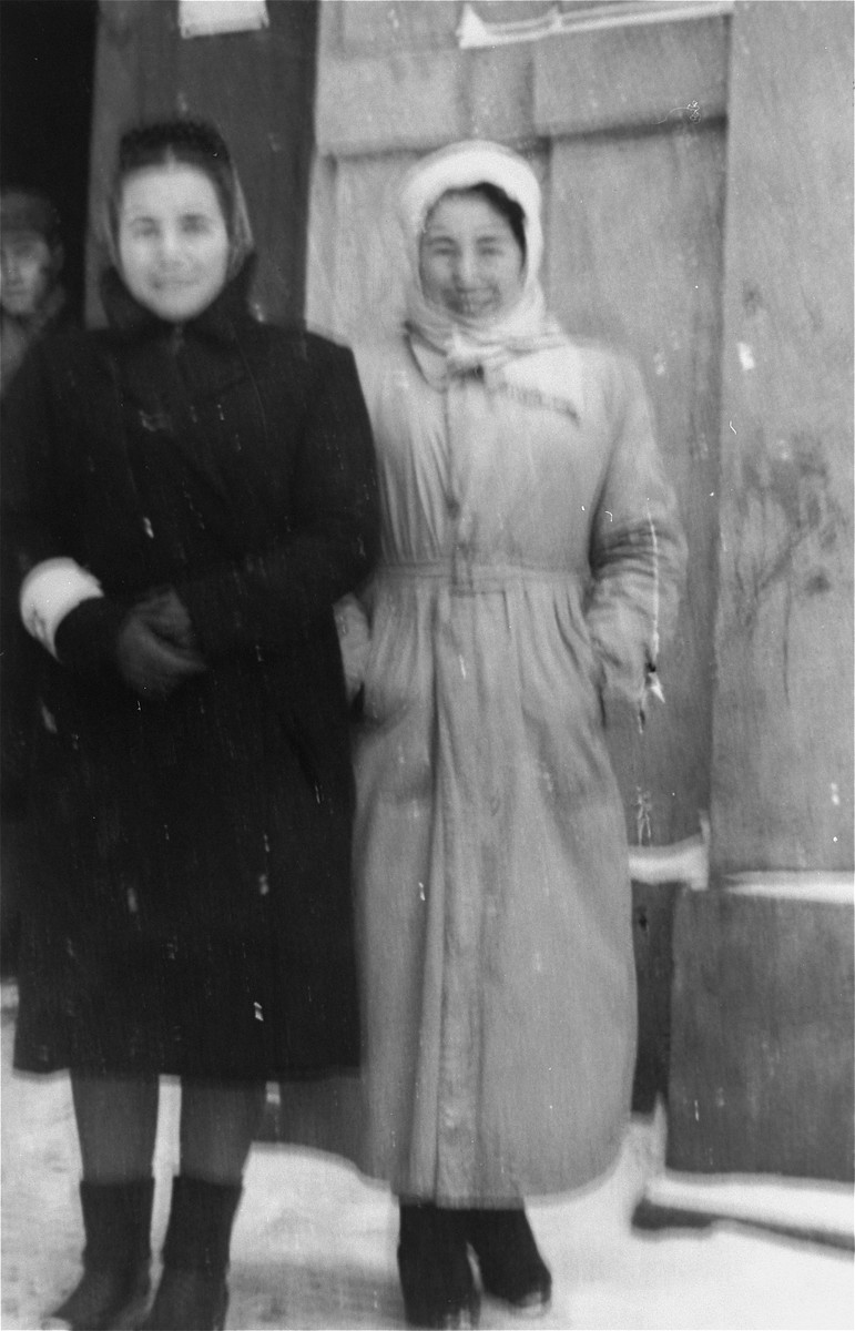 Two women wearing overcoats on a snow covered street in the Kielce ghetto.  This photo was one the images included in an official album prepared by the Judenrat of the Kielce ghetto in 1942.