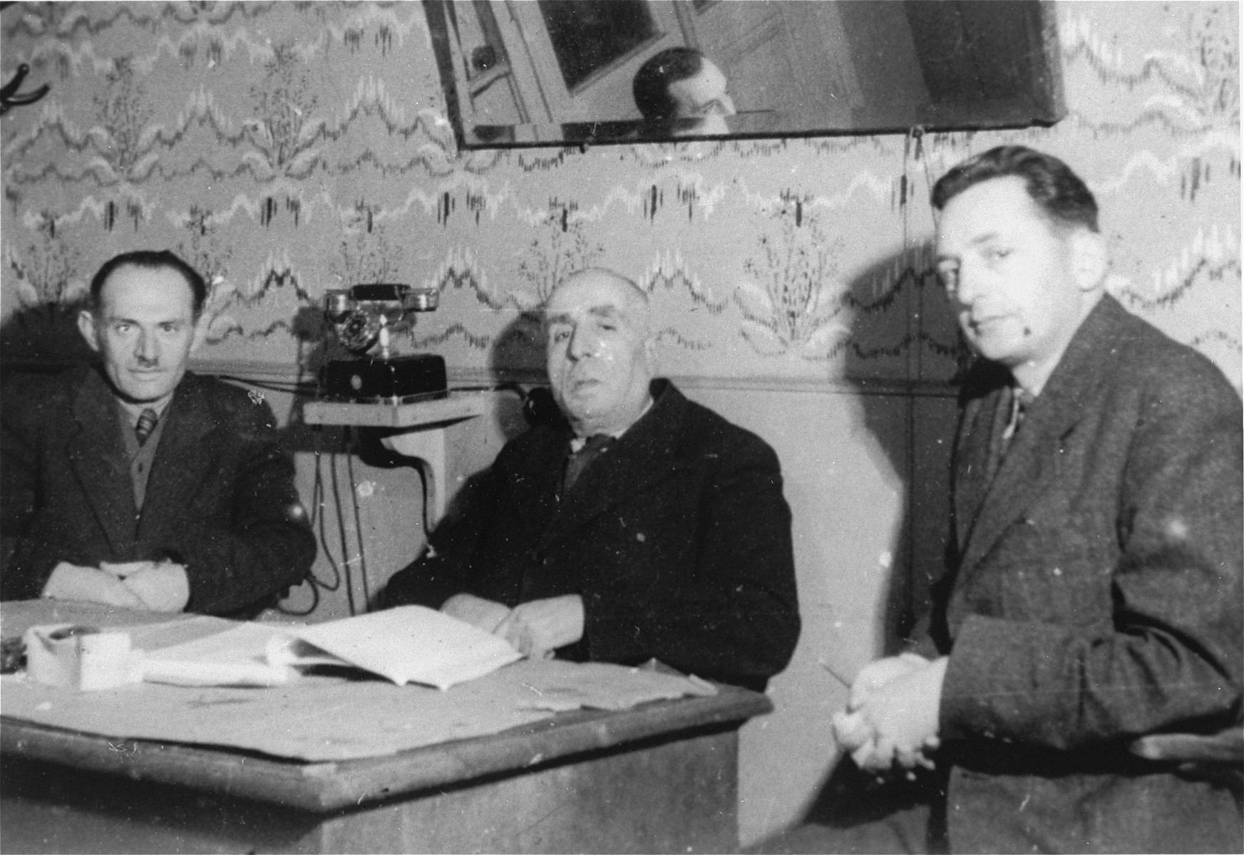 Three members of the ghetto administration sits around a table in the office of the Judenrat in the Kielce ghetto.  This photo was one the images included in an official album prepared by the Judenrat of the Kielce ghetto in 1942.