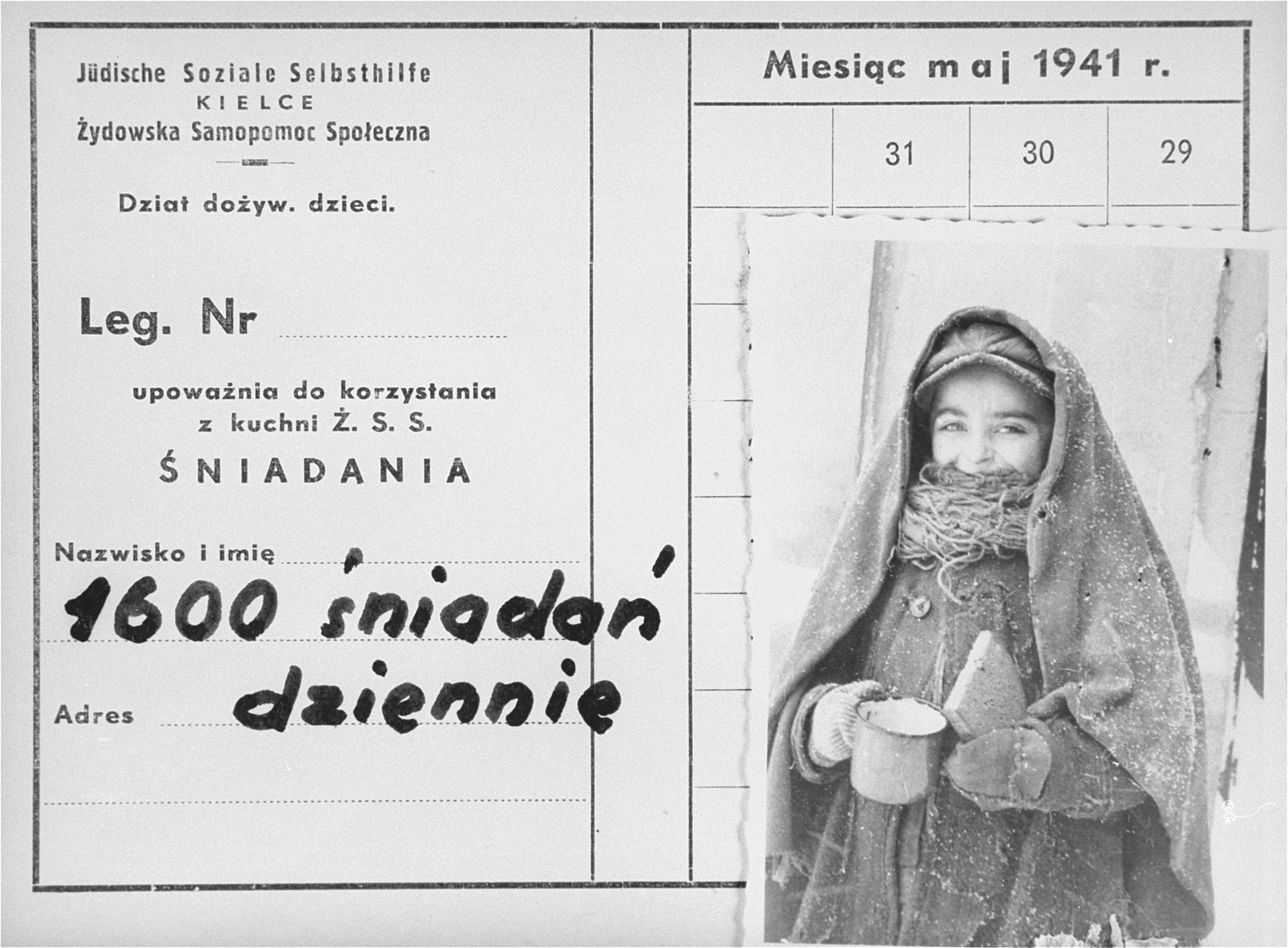 """An identification card bearing a photo of a child holding a cup and a piece of bread in the Kielce ghetto.   An official ID card was required to receive food rations at the soup kitchen organized by the Jewish Social Self-help Committee of the Jewish Council.  The ID card was issued for the month of May 1941, and was valid only for breakfast.  The inscription in Polish reads, """"1,600 morning meals served daily.""""  This photo was one the images included in an official album prepared by the Judenrat of the Kielce ghetto in 1942."""