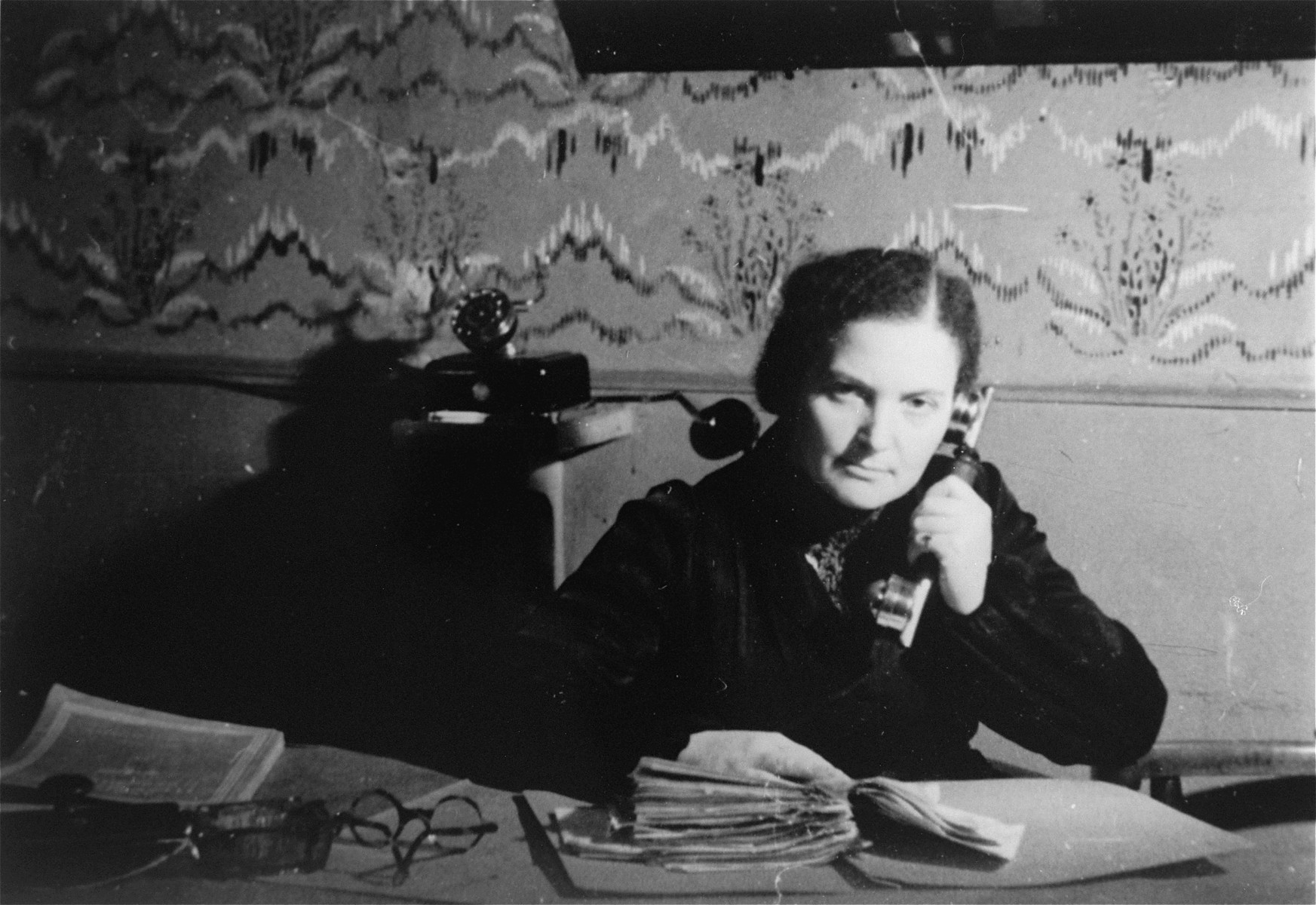 A female member of the ghetto administration sits at a desk in the office of the Judenrat in the Kielce ghetto.  This photo was one the images included in an official album prepared by the Judenrat of the Kielce ghetto in 1942.