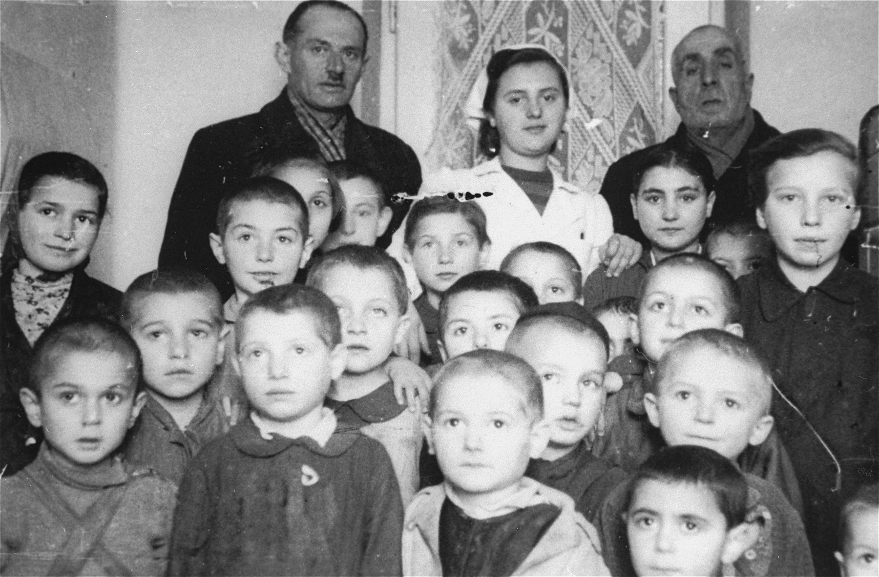 Group portrait of the children and staff of a daycare center in the Kielce ghetto that was administered by the Judenrat (Jewish Council).  This photo was one the images included in an official album prepared by the Judenrat of the Kielce ghetto in 1942.