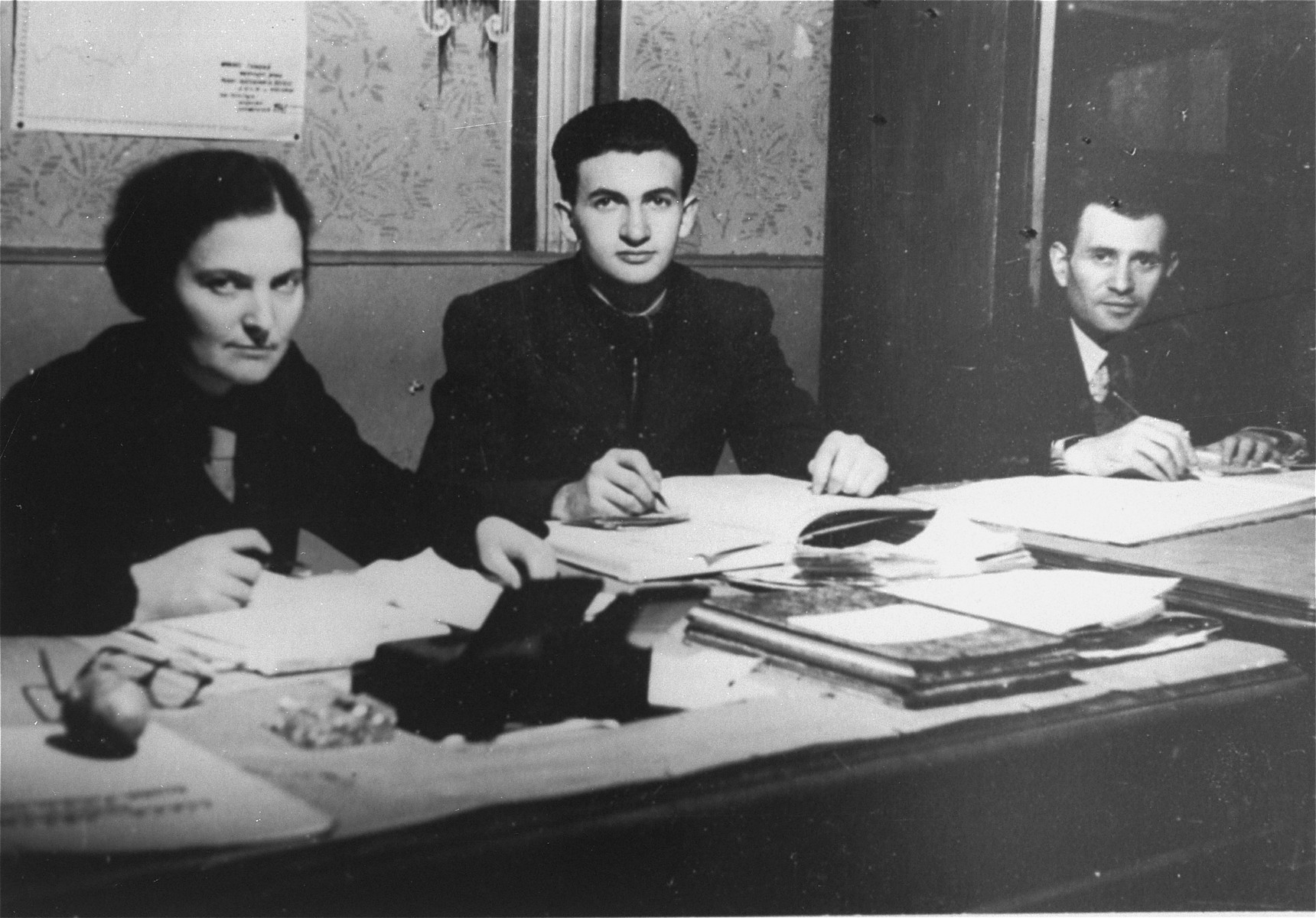 Three members of the administrative staff of the Kielce ghetto Judenrat (Jewish Council) at work in their office.  This photo was one the images included in an official album prepared by the Judenrat of the Kielce ghetto in 1942.