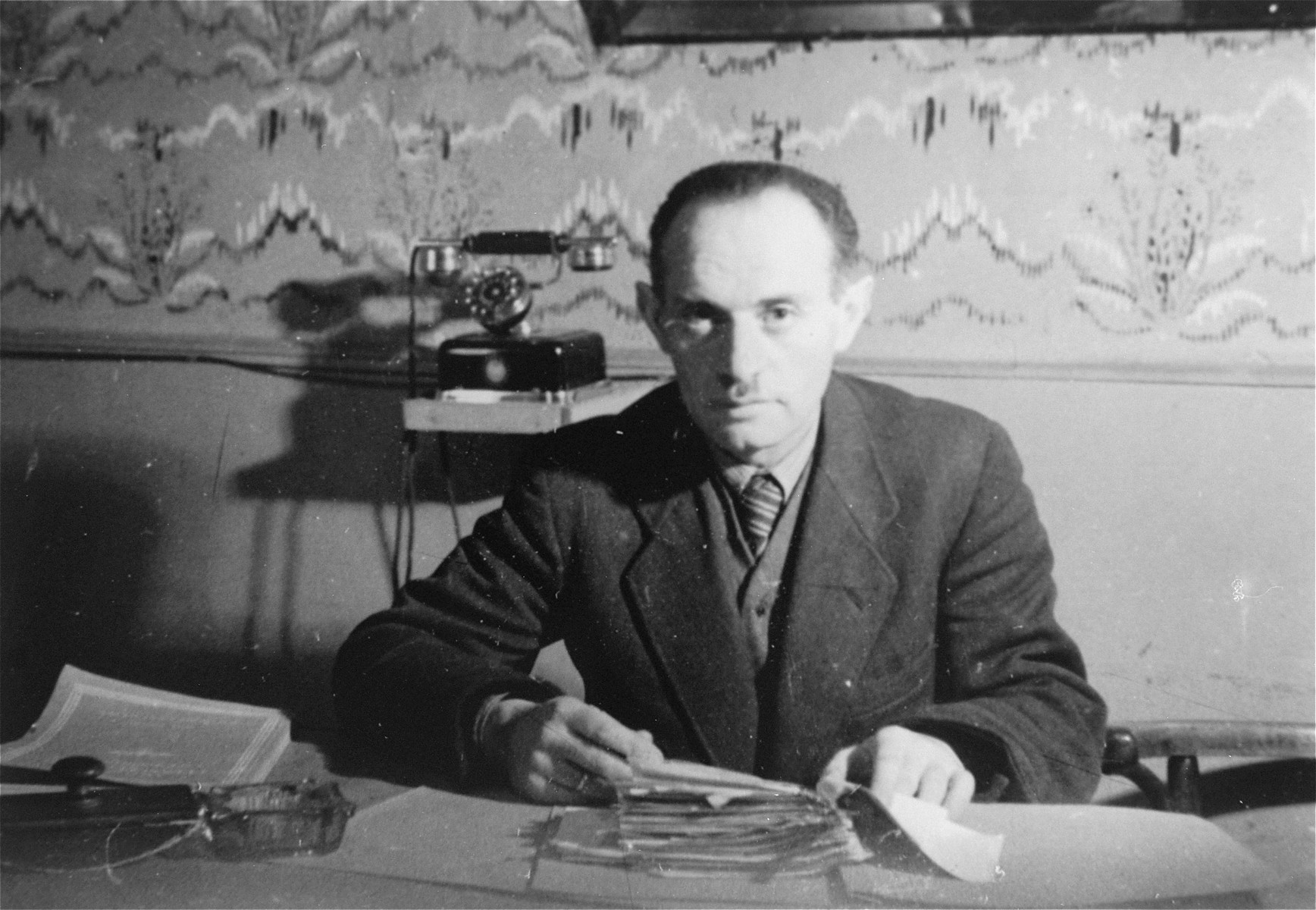 A member of the ghetto administration sits at a desk in the office of the Judenrat in the Kielce ghetto.  This photo was one the images included in an official album prepared by the Judenrat of the Kielce ghetto in 1942.