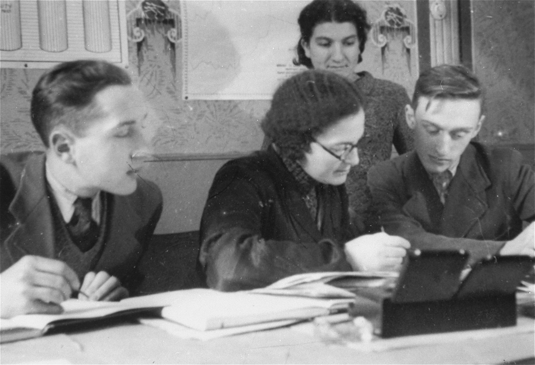Member of the ghetto administration at work in the office of the Judenrat in the Kielce ghetto.  This photo was one the images included in an official album prepared by the Judenrat of the Kielce ghetto in 1942.